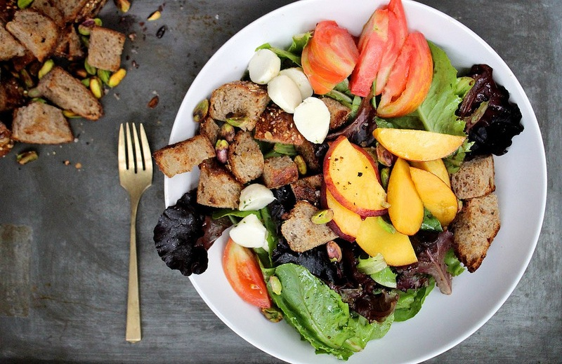 buttered bread croutons peach tomato pistachios salad