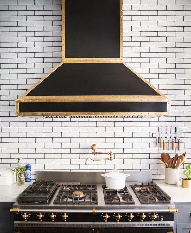 Ali Cayne NYC townhouse home Greenwich Village black gold stove kitchen