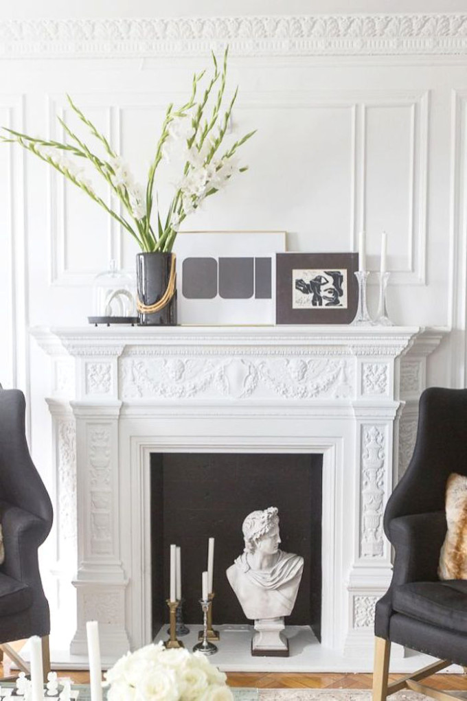 crown molding white fireplace black chairs