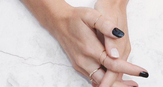 dainty gold rings and black and white nail polish manicure