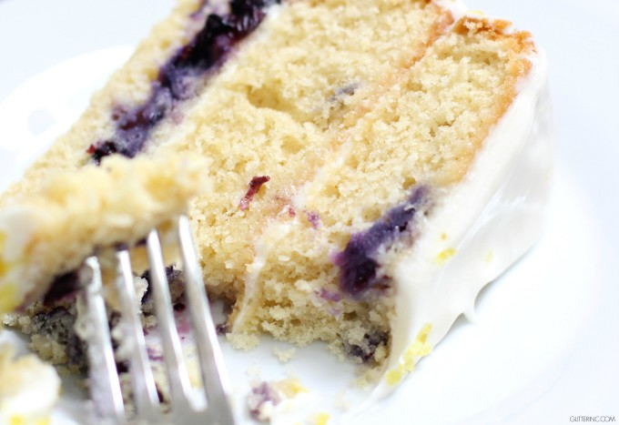 Three layers of moist, lemony cake, speckled with bursting blueberries, and spread with a melt-in-your-mouth icing. A ridiculously decadent cake that tastes light and summery all at the same time. Click through for the recipe. | glitterinc.com | @glitterinc