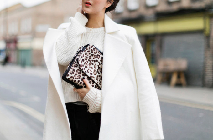 white coat, chunky knit crop sweater, and leopard clutch
