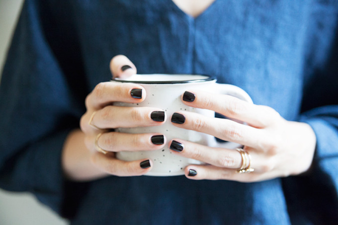 Why You Should Wear Black Nail Polish (black nail polish, gold rings, and a mug)