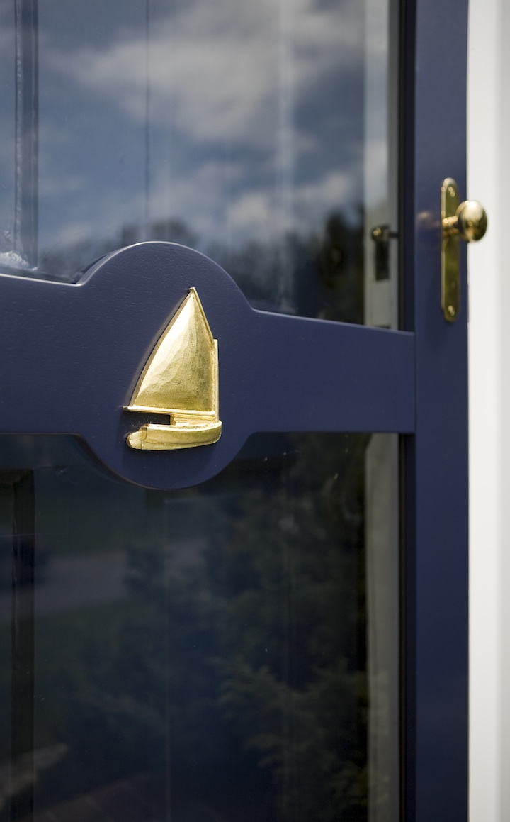 How to Upgrade Your Front Door with Modern Door Knockers (Brass Hardware and Sailboat on Navy Blue Storm Door)