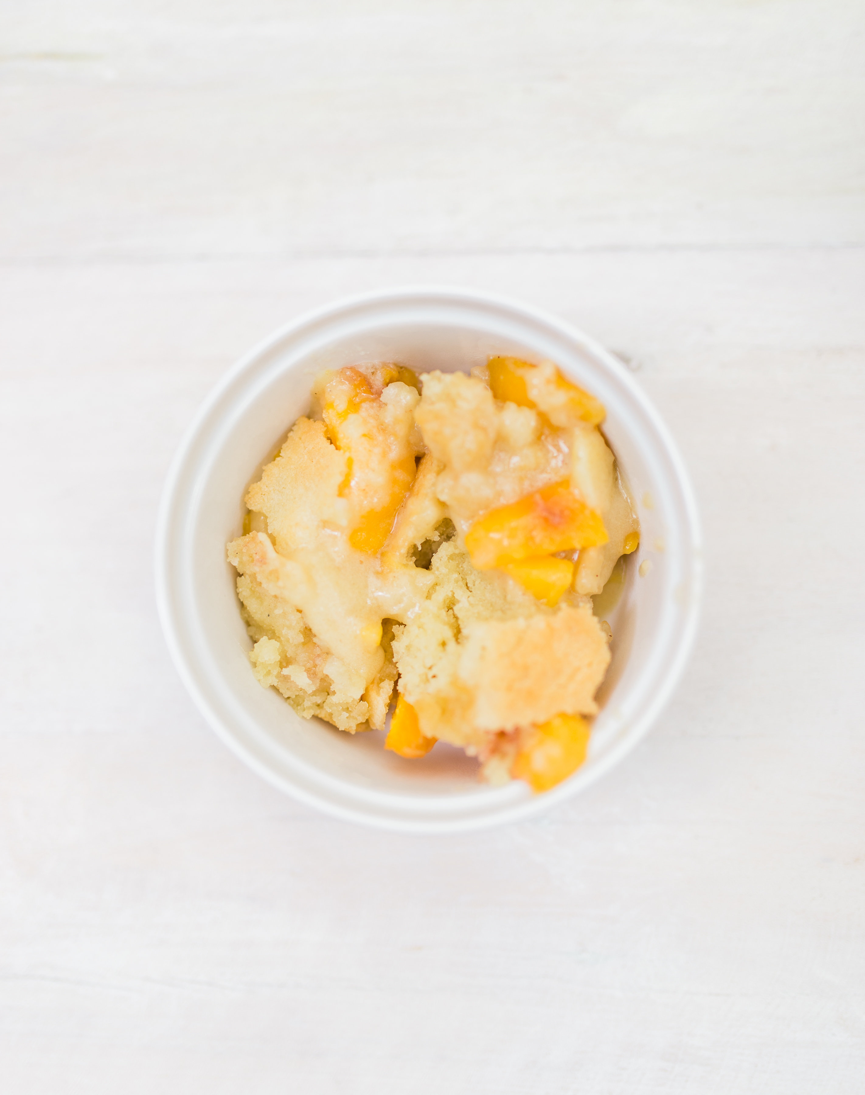 Foodie blogger Lexi of Glitter, Inc. shares a recipe for classic peach cobbler. Caramelized peaches are topped with a sugar-cookie-like doughy crust. YUM. | glitterinc.com | @glitterinc