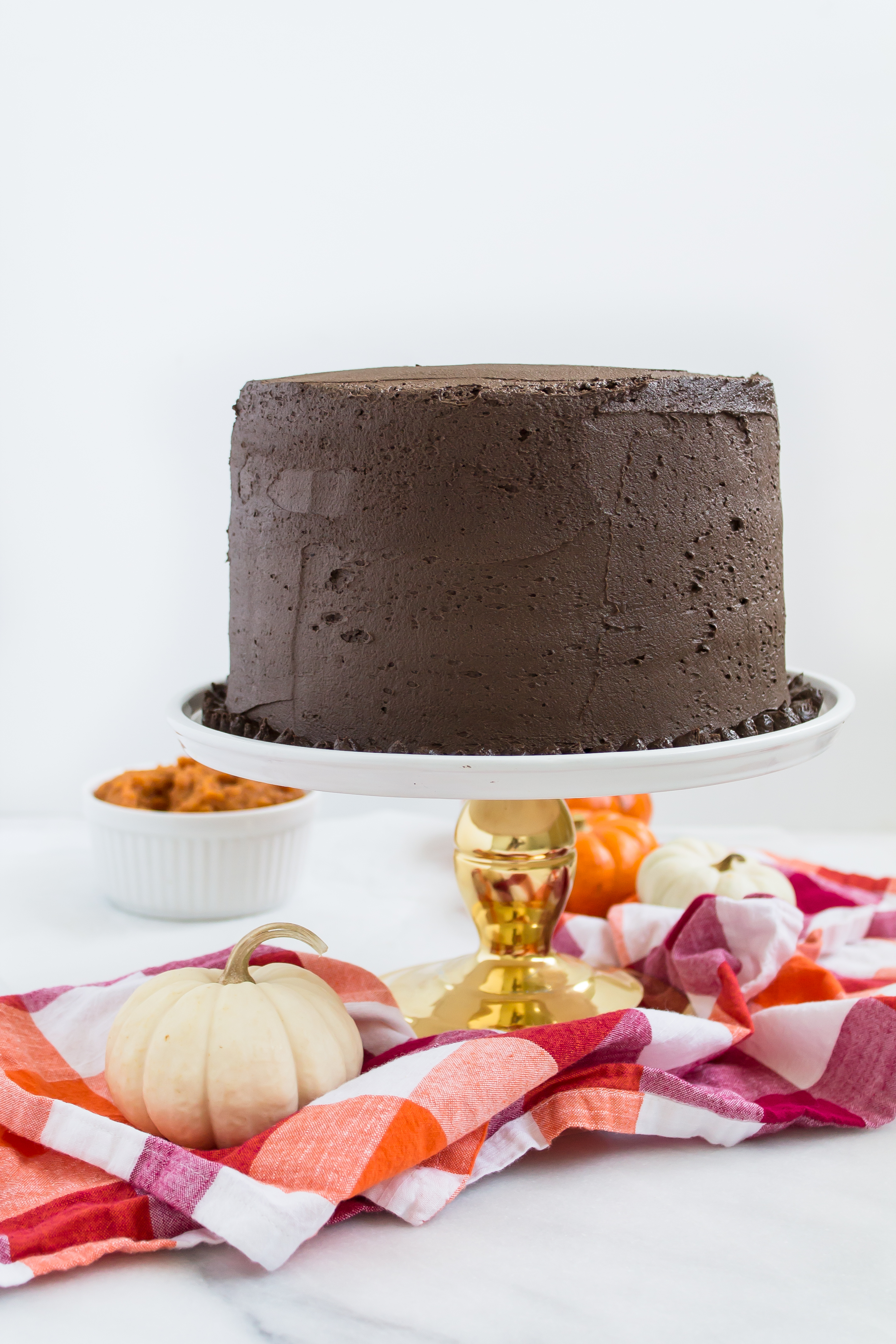 This incredibly moist spiced pumpkin cake topped with a rich and fluffy chocolate frosting is perfect for fall. Click through for the recipe. | glitterinc.com | @glitterinc - Pumpkin Cake Recipe with Fluffy Chocolate Frosting by North Carolina foodie blogger Glitter, Inc.