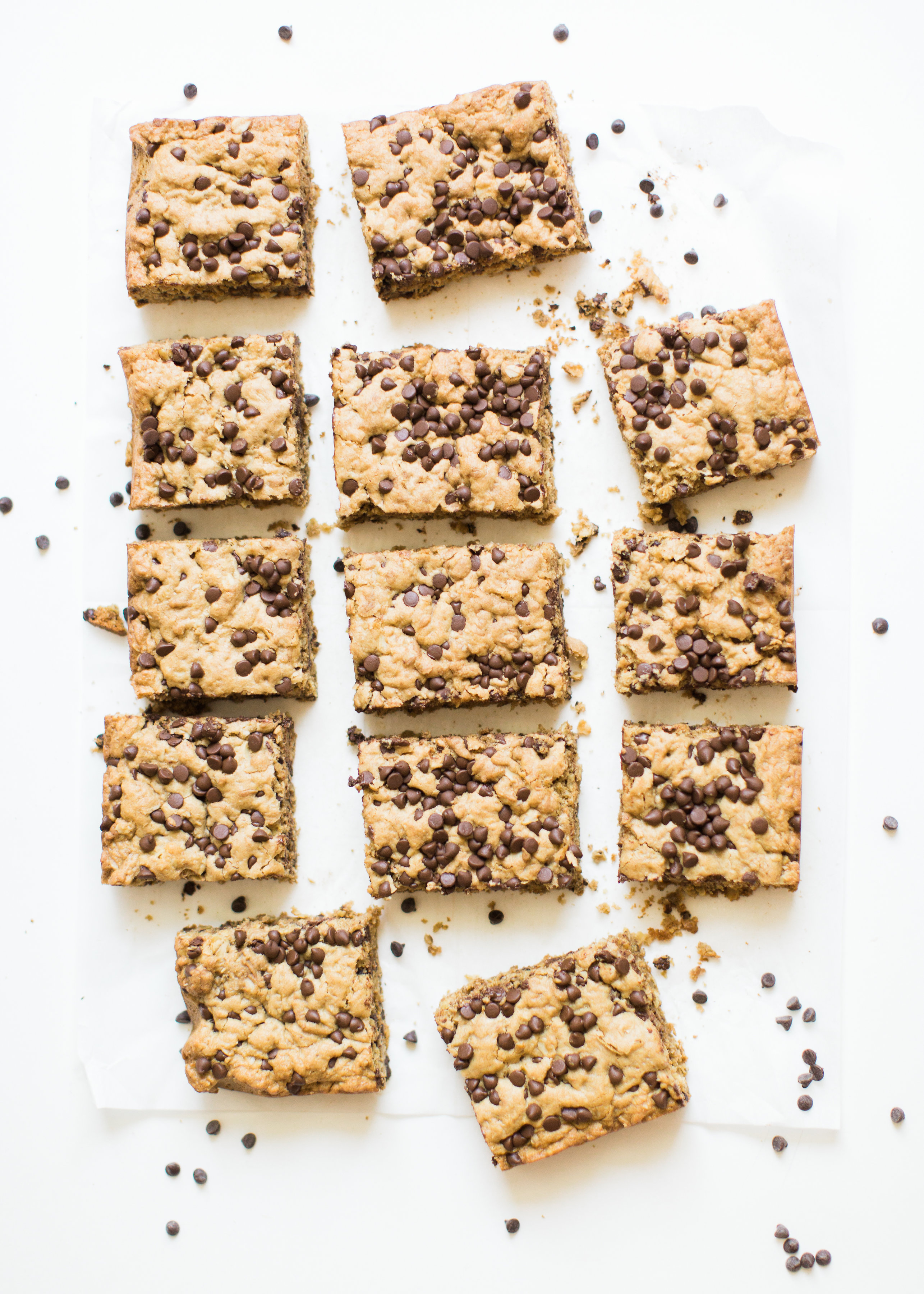 Delicious chocolate chip oatmeal cookies made extra simple by baking them up in a big batch of bars, these super moist chocolate chip oatmeal cookie bars are a favorite of our whole family, and for good reason! Click through for the #recipe. #oatmealcookies #oatmealcookiebars #cookiebars  #oatmealcookierecipe #dairyfree | glitterinc.com | @glitterinc