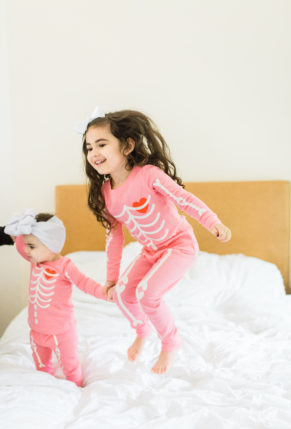 Scarlett and Emmeline – 4 and 1 Years Old – Girls in Matching Pink Halloween Skeleton Pajamas