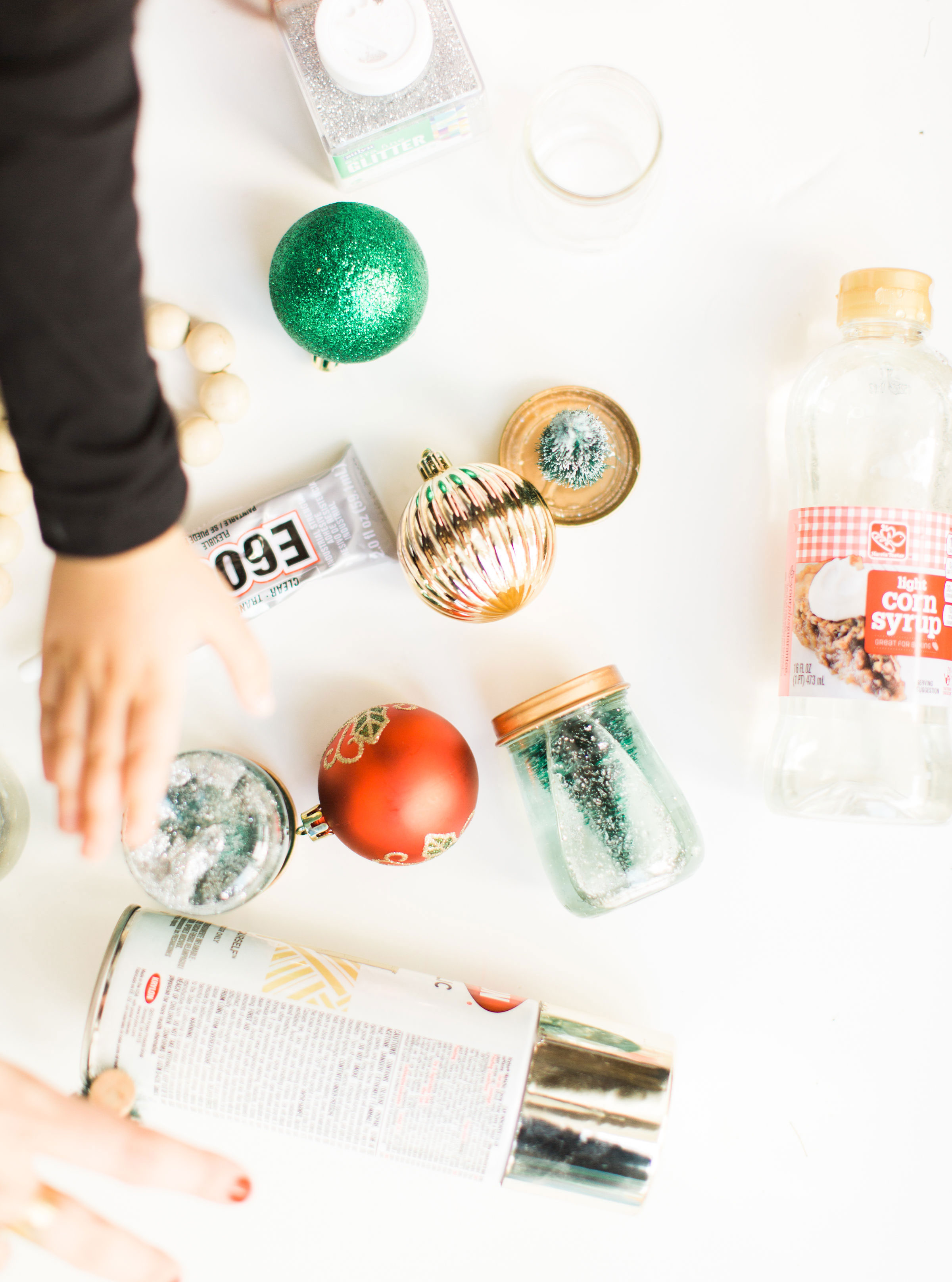 Glitter DIY snow globes are fun to make, are a great craft to do with kids, and double as a calm down sensory bottle for a little quiet time on days when the whole family is going a little stir crazy! Click through for the details. #kidsdiy #kidscraft #diysnowglobes #howtomakesnowglobes #sensorybottles #sensoryglobes #toddlercraft #wintercraft #christmas #christmasdiy #christmascraft | glitterinc.com | @glitterinc