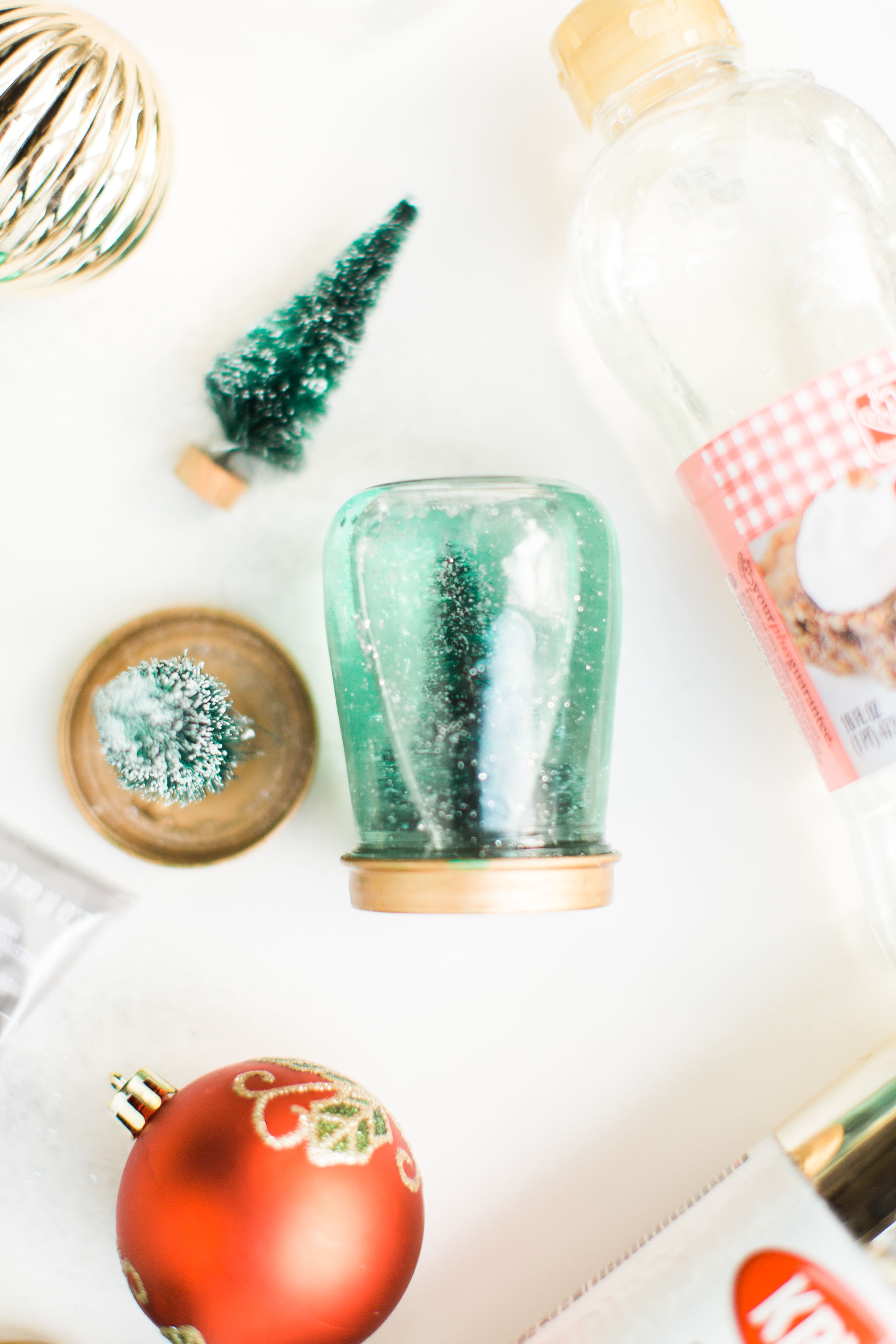 Glitter DIY snow globes are fun to make, are a great craft to do with kids, and double as a calm down sensory bottle for a little quiet time on days when the whole family is going a little stir crazy! Click through for the details. #kidsdiy #kidscraft #diysnowglobes #howtomakesnowglobes #sensorybottles #sensoryglobes #wintercraft #christmas #christmasdiy #christmascraft | glitterinc.com | @glitterinc