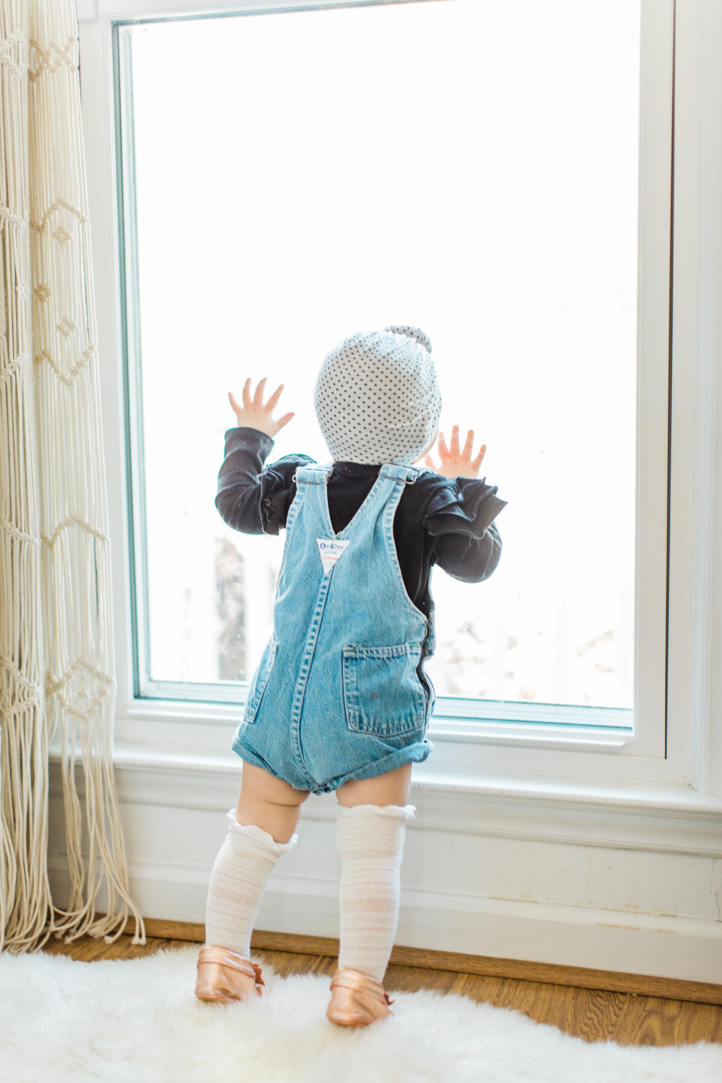 Baby girl is wearing OshKosh B'Gosh overalls