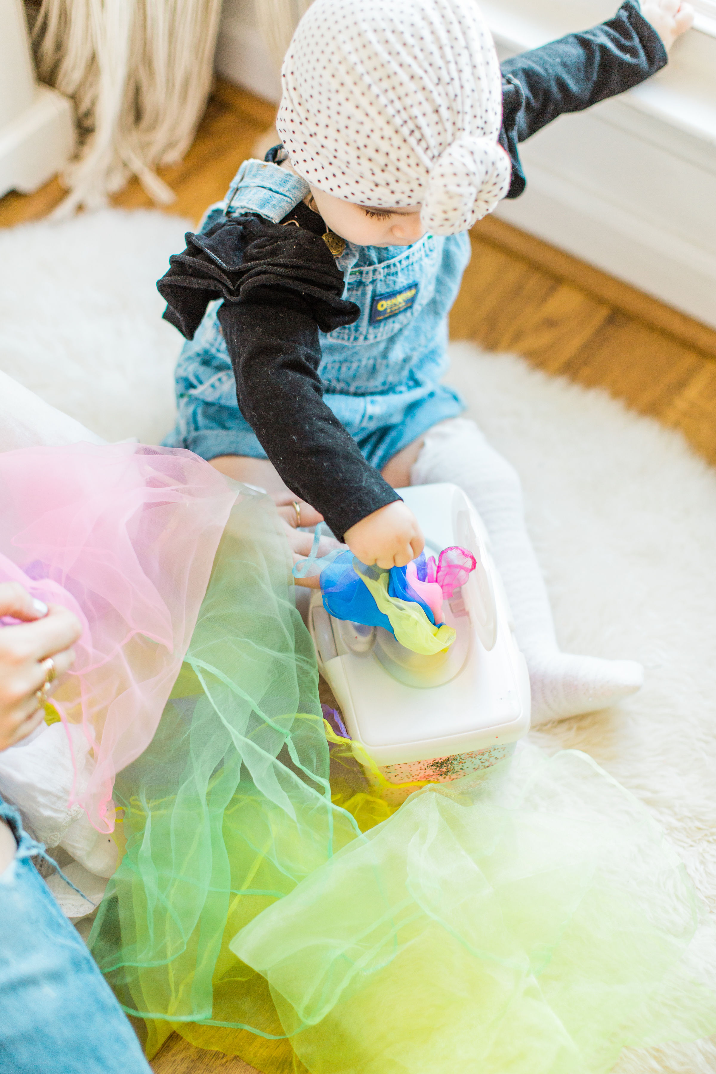 Looking for a fun activity to do with your baby? Make an easy, magic sensory toy using an empty wipes container and inexpensive colorful scarves. | Click through for the DIY. | glitterinc.com | @glitterinc