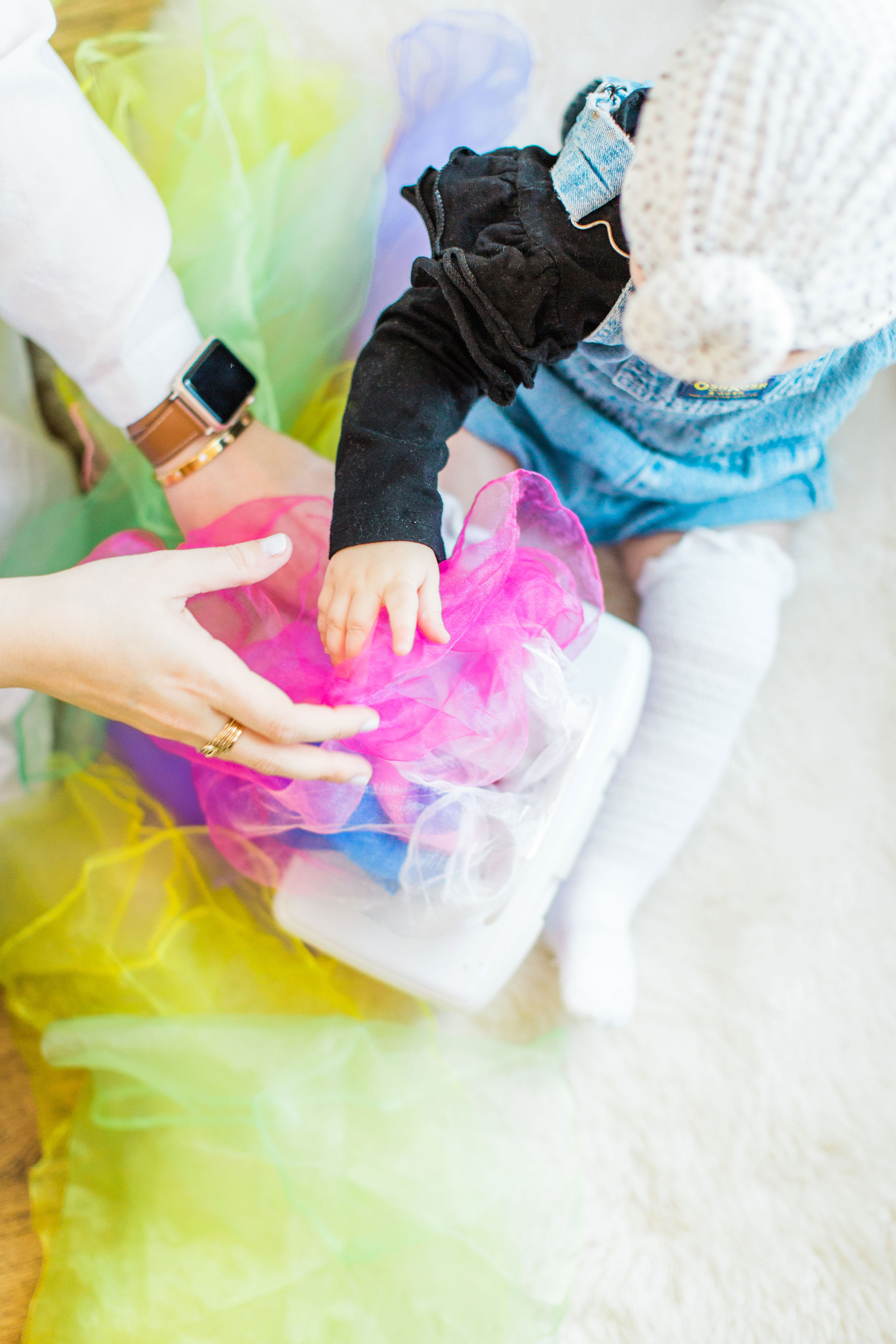 Looking for a fun activity to do with your baby? Make an easy, magic sensory toy using an empty wipes container and inexpensive colorful scarves.