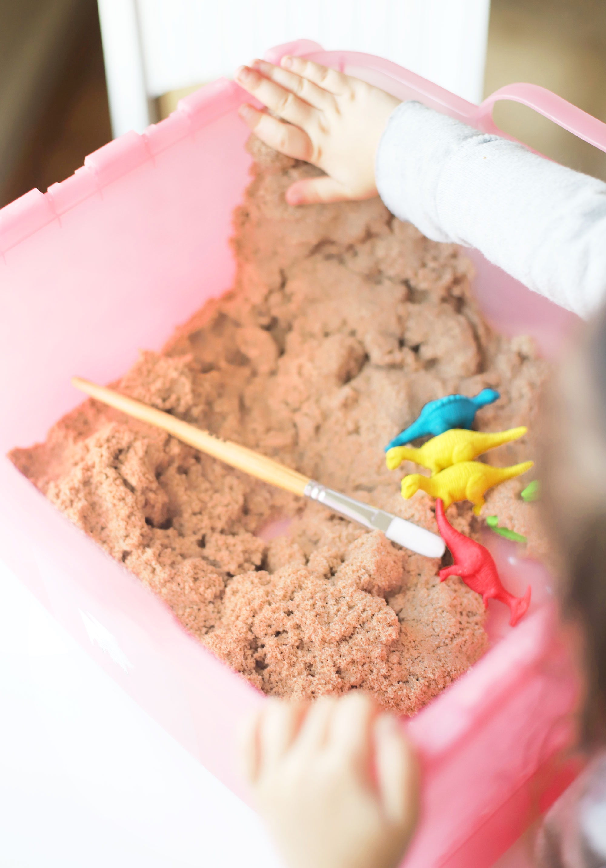 Create your own DIY kinetic sand dinosaur dig. This kids activity is an awesome, mostly mess-free way to dig into sensory play, all in one convenient bin.