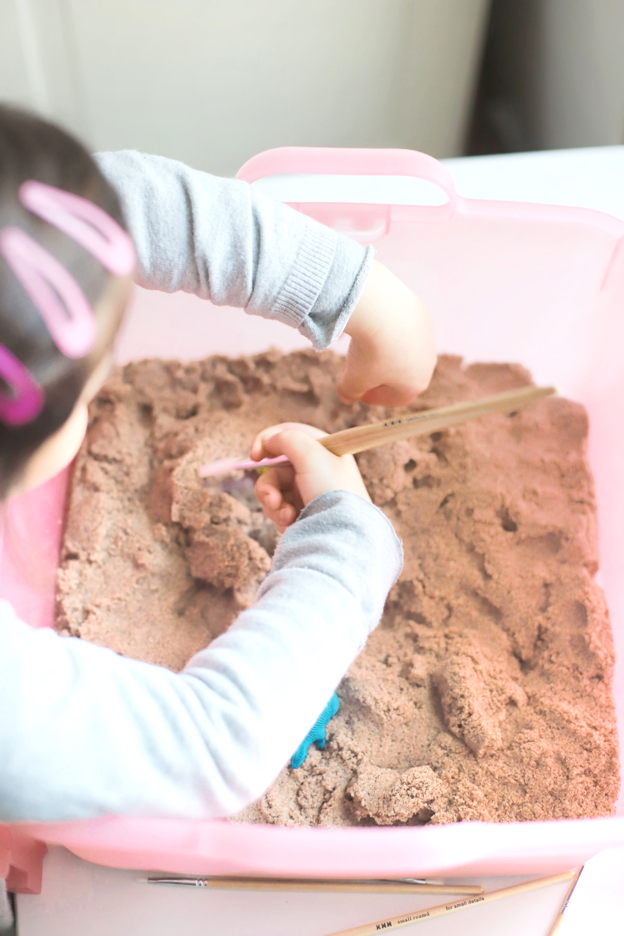 Create your own DIY kinetic sand dinosaur dig. This kids activity is an awesome, mostly mess-free way to dig into sensory play, all in one convenient bin.  glitterinc.com | @glitterinc