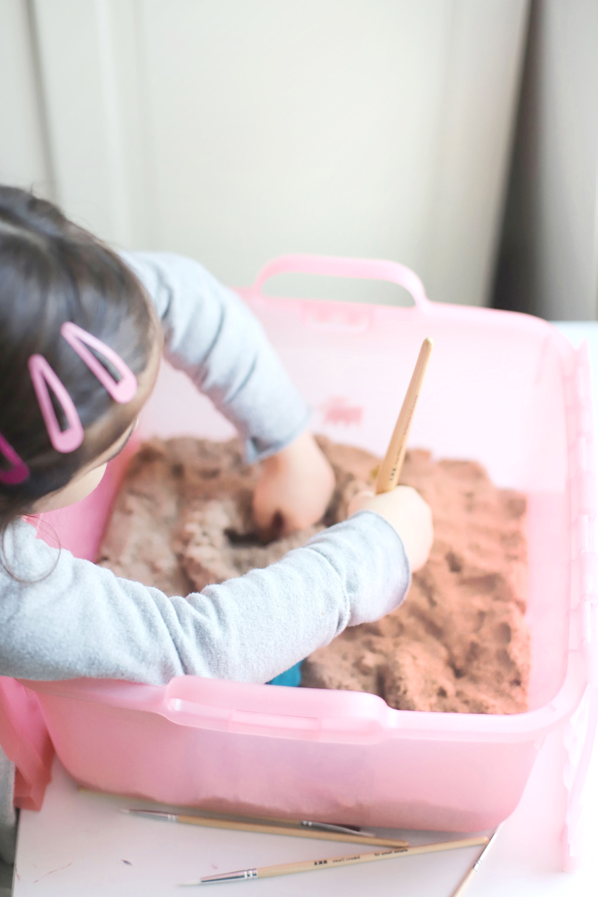 Create your own DIY kinetic sand dinosaur dig. This kids activity is an awesome, mostly mess-free way to dig into sensory play, all in one convenient bin