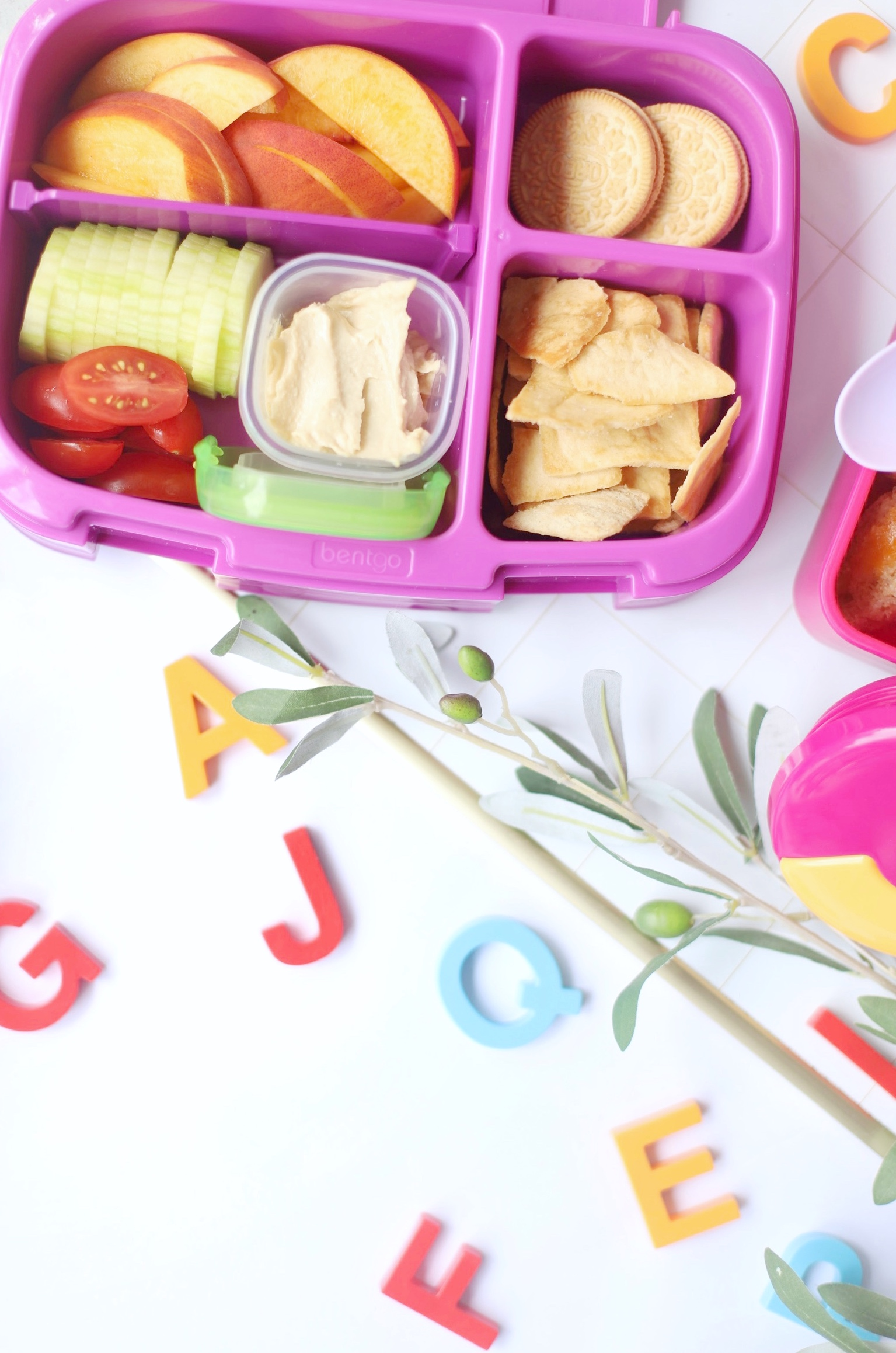 a lunch kit with crackers and tomatoes and apples