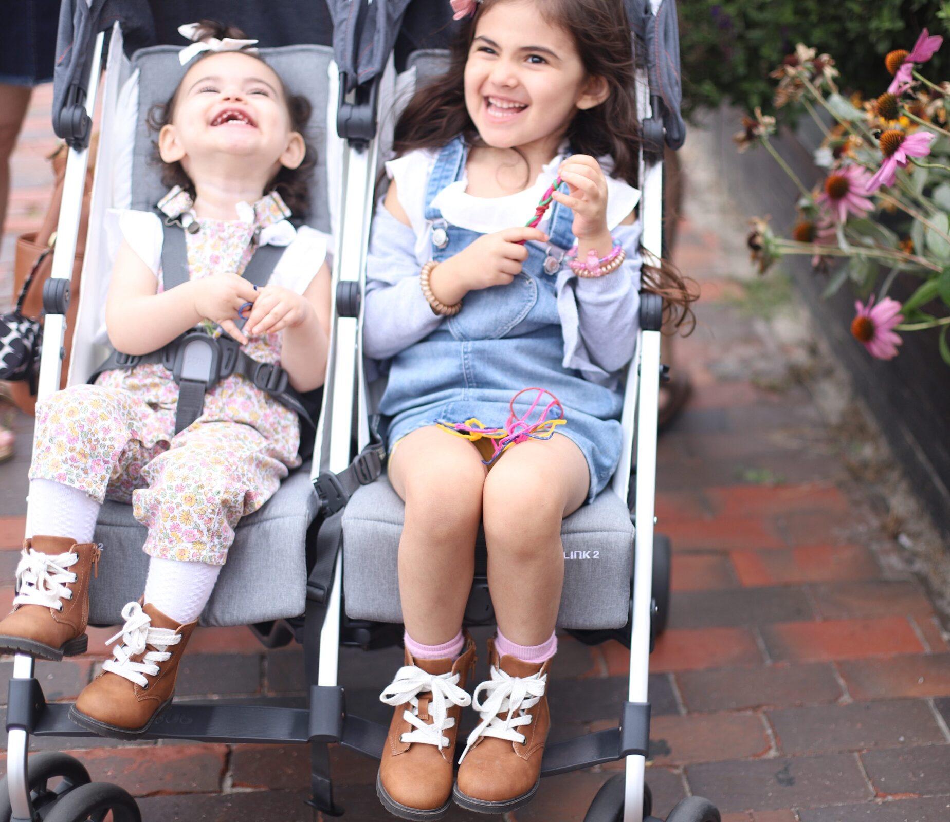 happy two kids in a double stroller