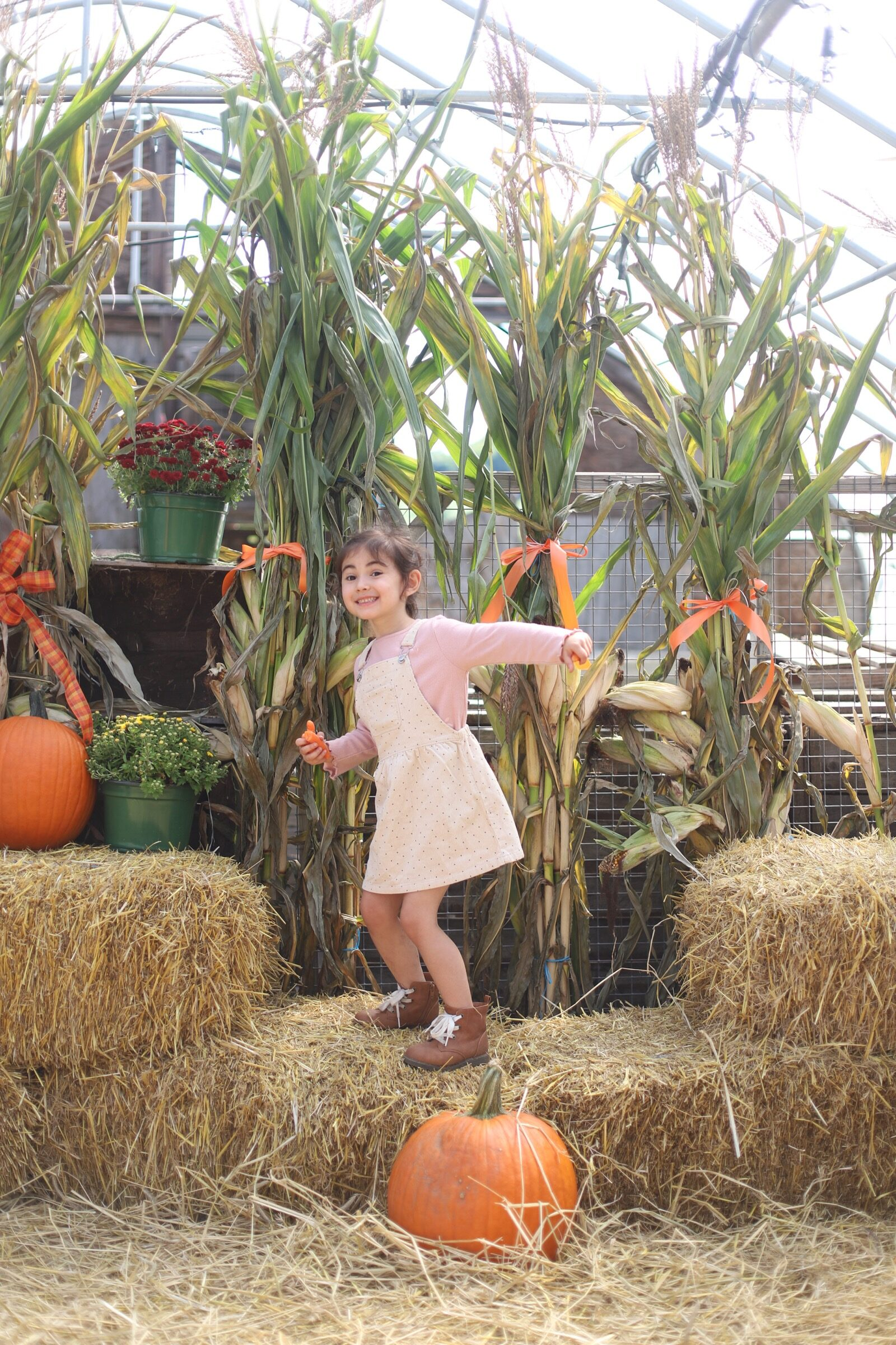 A little girl posing with haystacks and pumpkins at Brooksby Farm in Peabody, Massachusetts // Fall Bucket List | glitterinc.com | @glitterinc