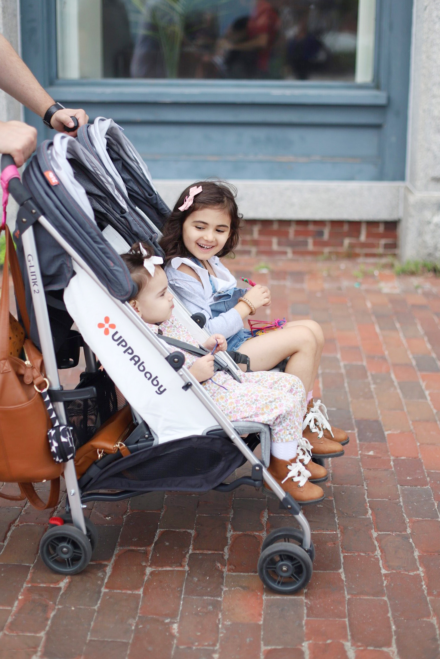 a parent pushing Two kids in lightweight double stroller from UPPAbaby G-LINK 2
