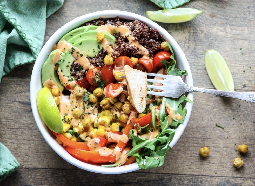 The ingredients for these healthy burrito bowls start out on a sheet pan. Everything gets roasted together, including the crispy chickpeas, before being assembled in bowls.