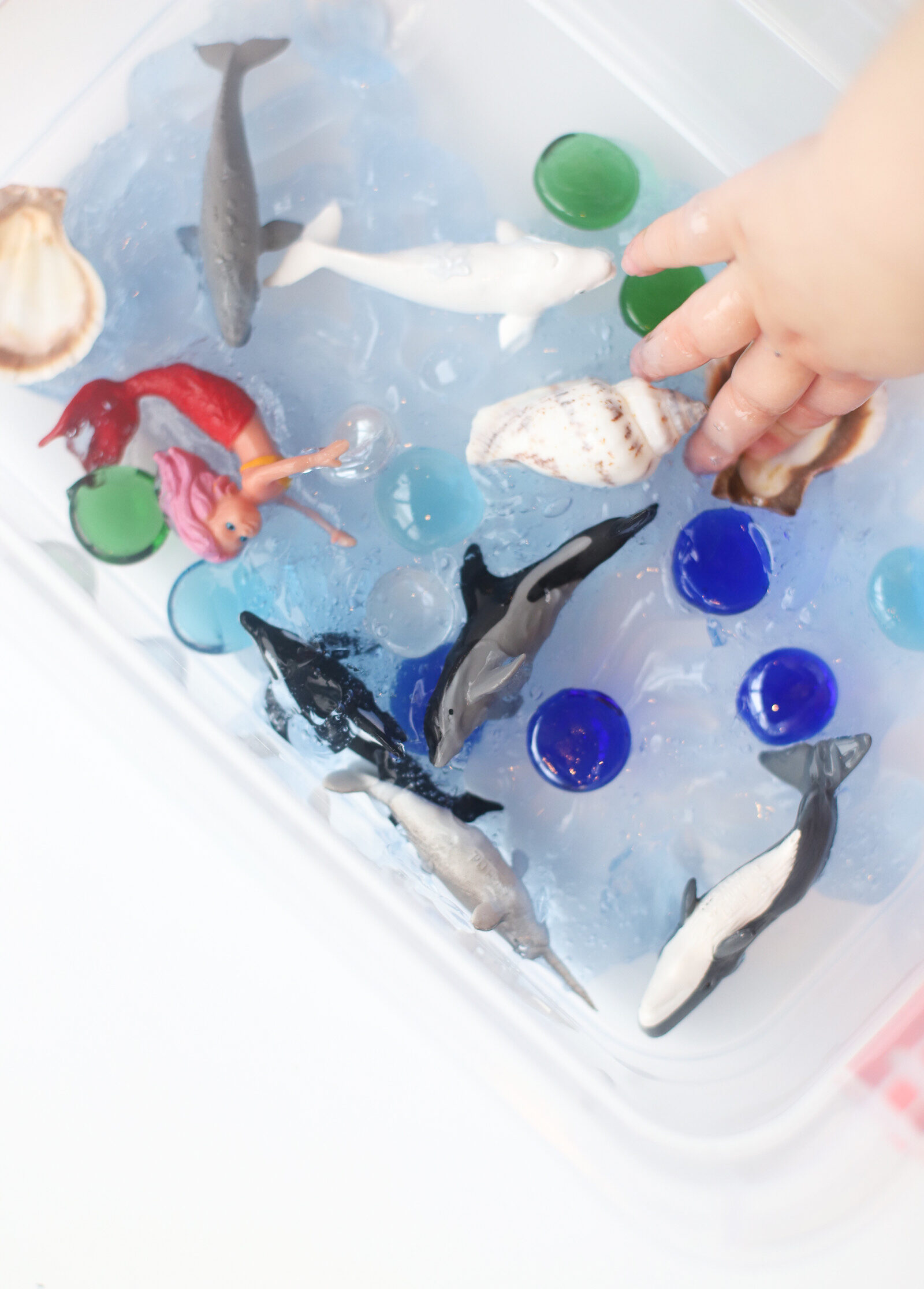 Home with your young kids? Here is a huge list of fun and educational activities to do at home with young kids, including exactly how to entertain your children during school closures, cold and flu days, Spring and Summer vacation breaks, and more. | glitterinc.com | @glitterinc // Make your kids an Easy and Fun Kids Ocean Sensory Bin Activity with inexpensive items and watch their imaginations run wild! Plus, a no mess option, and how to store and re-use the DIY ocean sensory bin again and again. This craft is a perfect learning activity for toddlers, preschools, kindergarteners, and beyond!