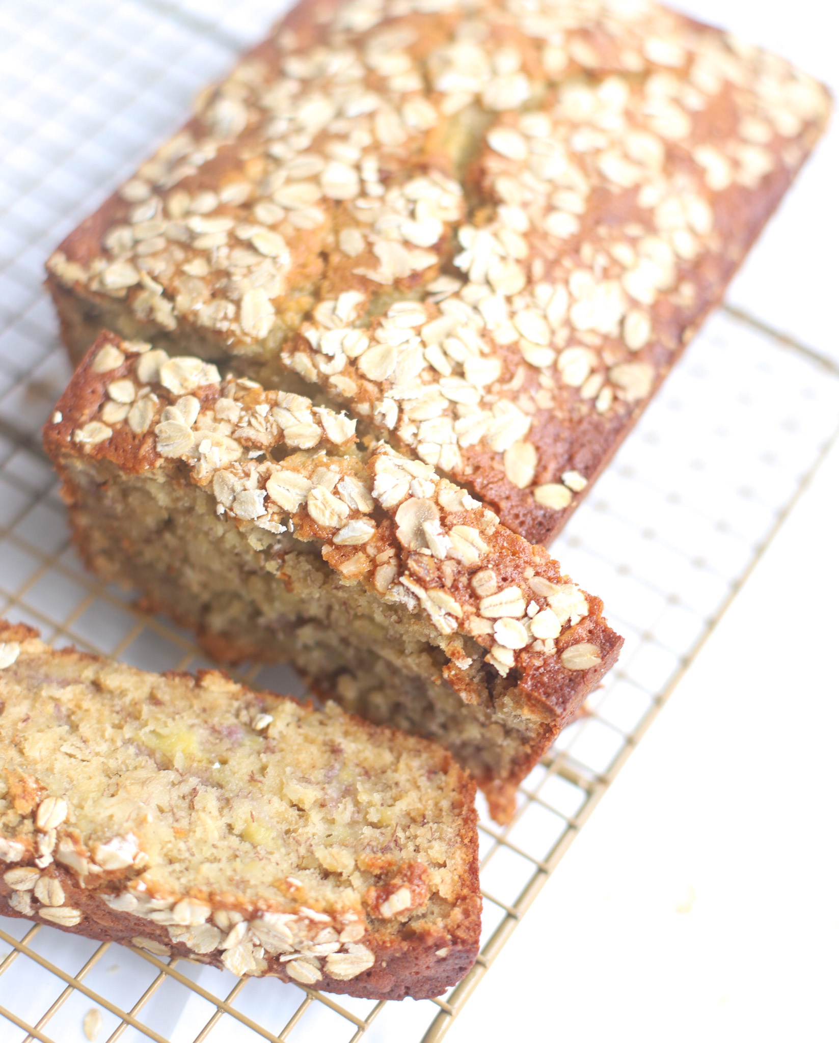 Oatmeal banana bread is the most amazing twist on a more classic banana quick bread. Filled with oats and yogurt, the recipe results in a delicious banana bread that is fluffy, moist, and has the perfect chewy crust. Click through for the recipe. | glitterinc.com | @glitterinc