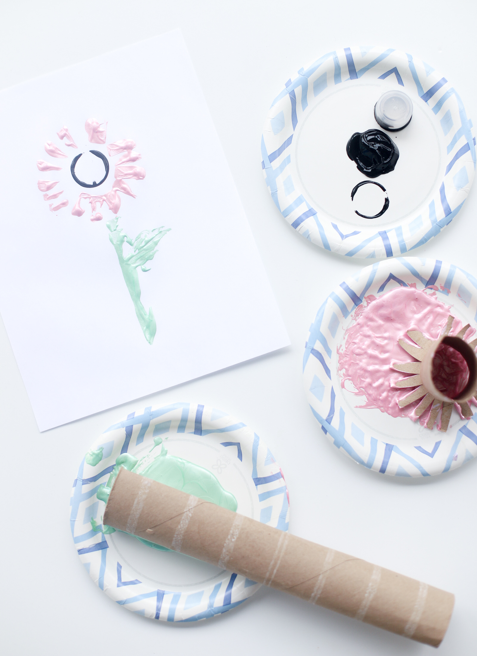Make adorable stamp flower works of art using recycled materials like toilet paper rolls, paper towel rolls, and plastic bottle caps. This toilet paper flower stamping craft is fun for kids of all ages and the end result makes a perfect gift! | @glitterinclexi | GLITTERINC.COM