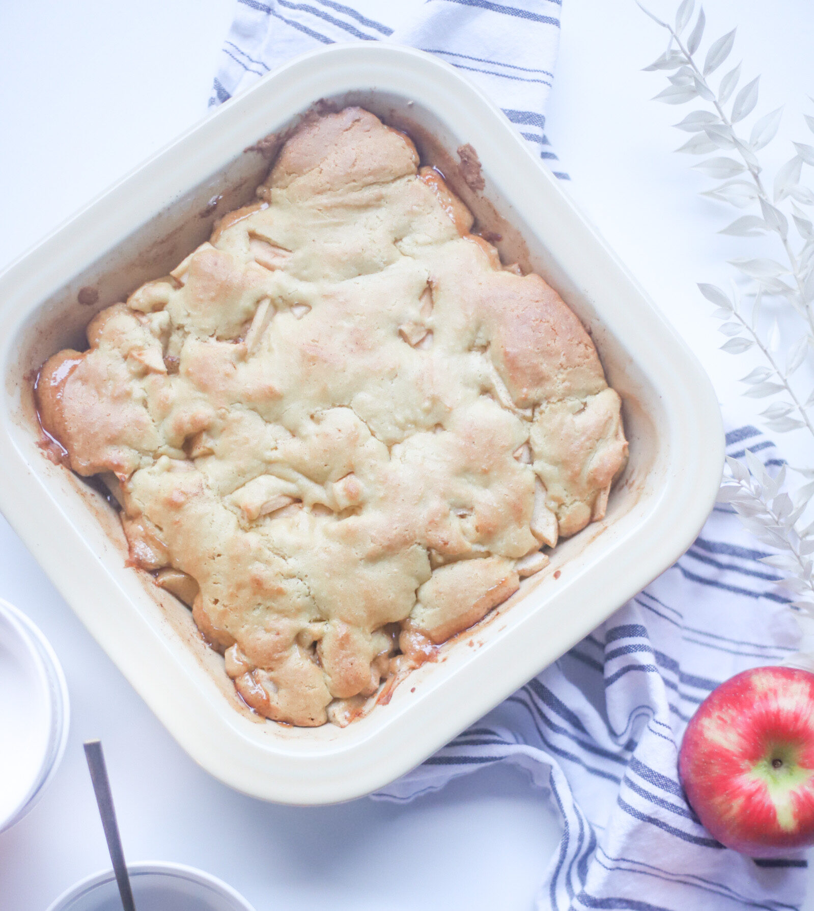 This deceptively delicious apple cobbler is full of cinnamon, fragrant apples, and a velvety caramel sauce, topped with the most heavenly dough, and yet, is actually lower calorie than a traditional cobbler and can also be made dairy-free! Click through for the fall recipe. | @glitterinclexi | GLITTERINC.COM