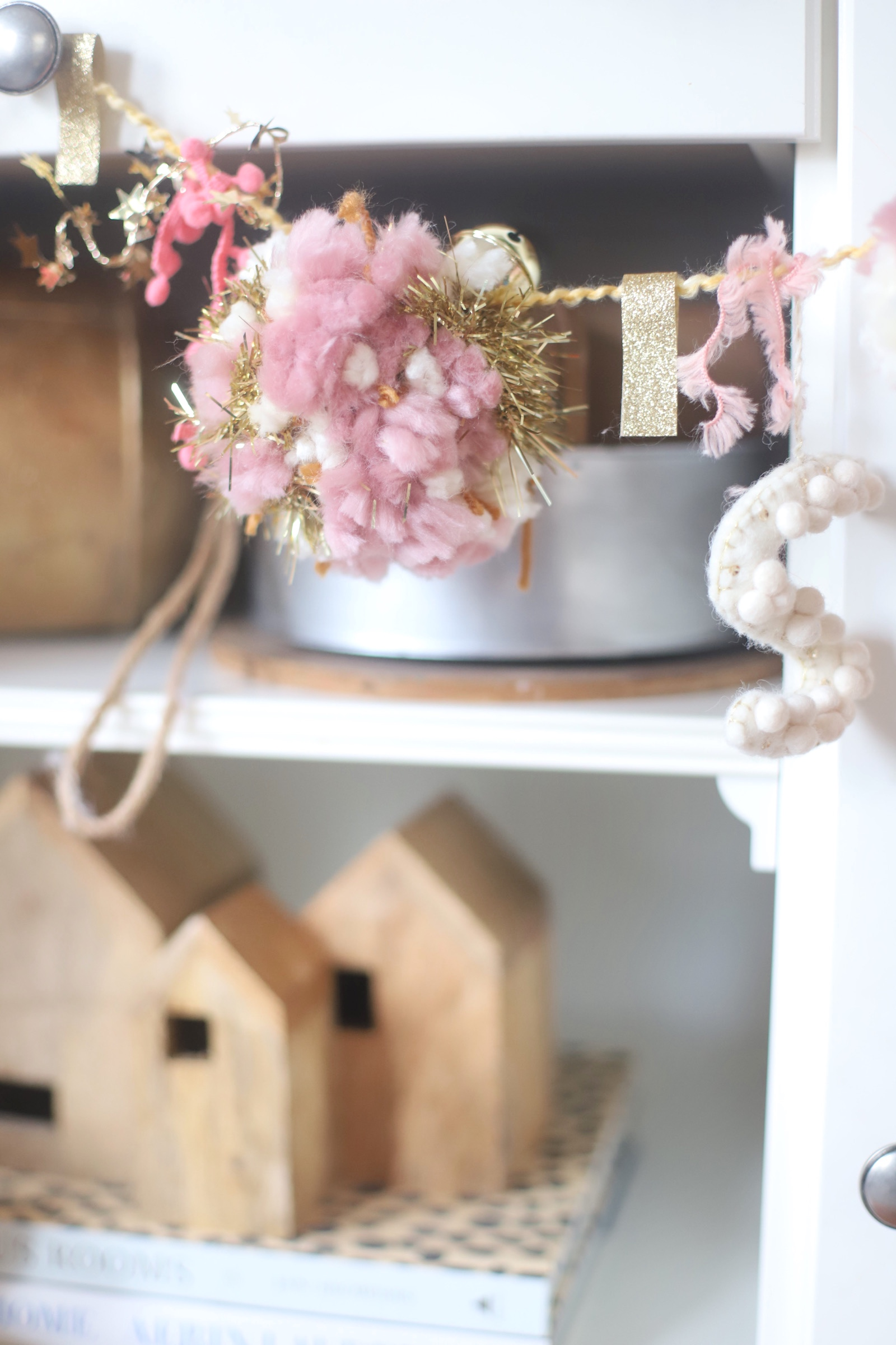 Make your own boutique-worthy DIY Embellished pom pom garland with festive tinsel, ribbon, washi tape, gold bells, and glitter stars; a.k.a., a glammed up pom pom garland with a whole lot of pizazz.| @glitterinclexi | GLITTERINC.COM