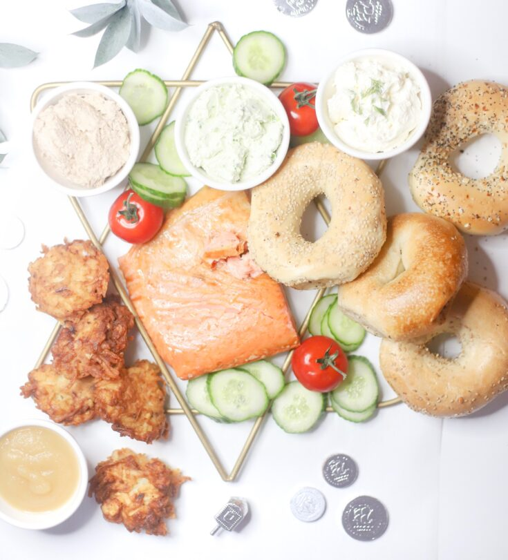 Celebrating Hanukkah this year? Make an easy and festive Chanukah dinner charcuterie complete with a simple board of bagels, smoked fish, latkes, and all of the fixings. | @glitterinclexi | GLITTERINC.COM
