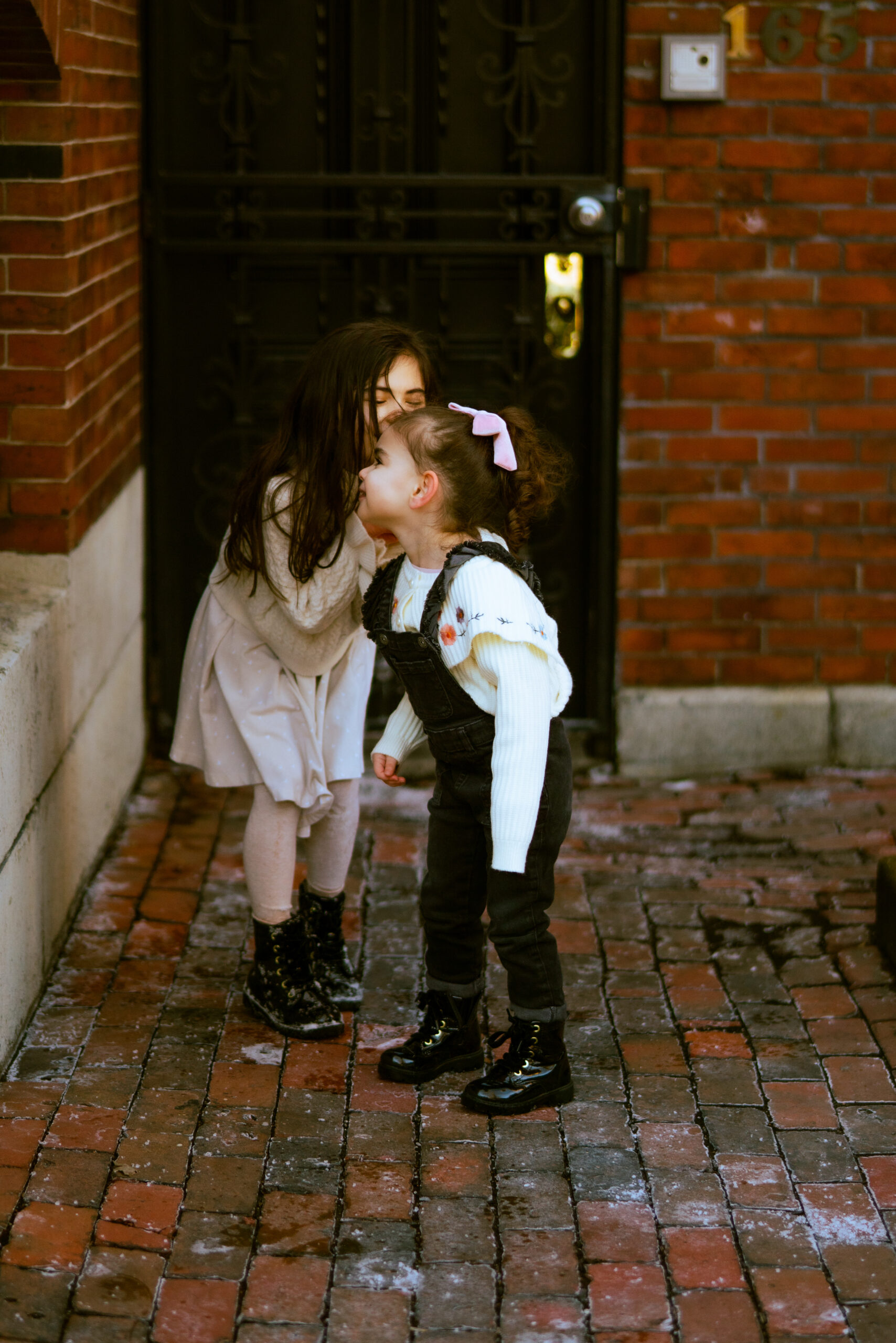 a little girl whispering to her sister