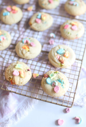 The best and most unbelievably perfect dairy free sugar cookies, filled and topped with Lucky Charms marshmallows, plus a soft, thick, and chewy interior; these festive pillowy sugar cookies are a deliciously adorable recipe for a St. Patrick's Day treat. | @glitterinclexi | GLITTERINC.COM
