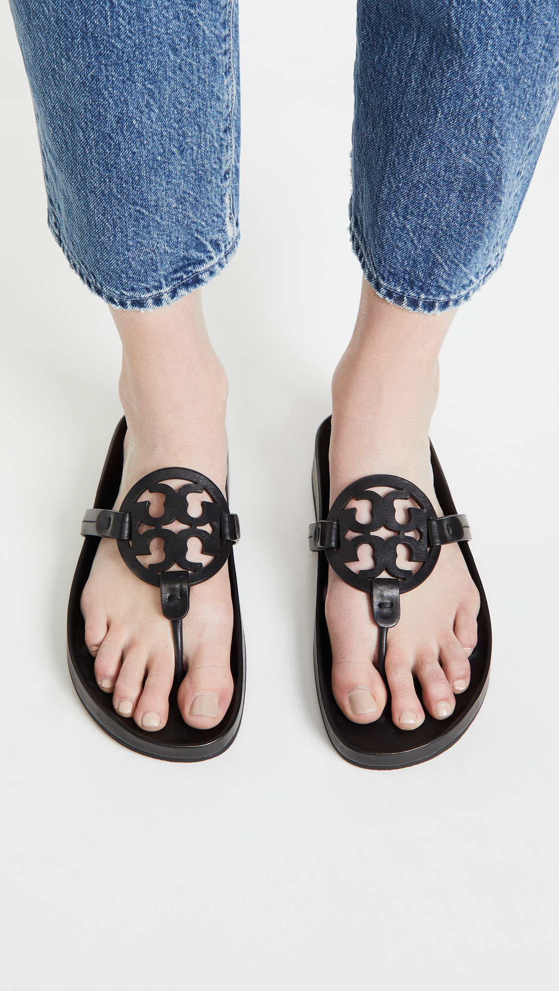 woman wearing Tory Burch Miller Cloud Sandals and blue jeans