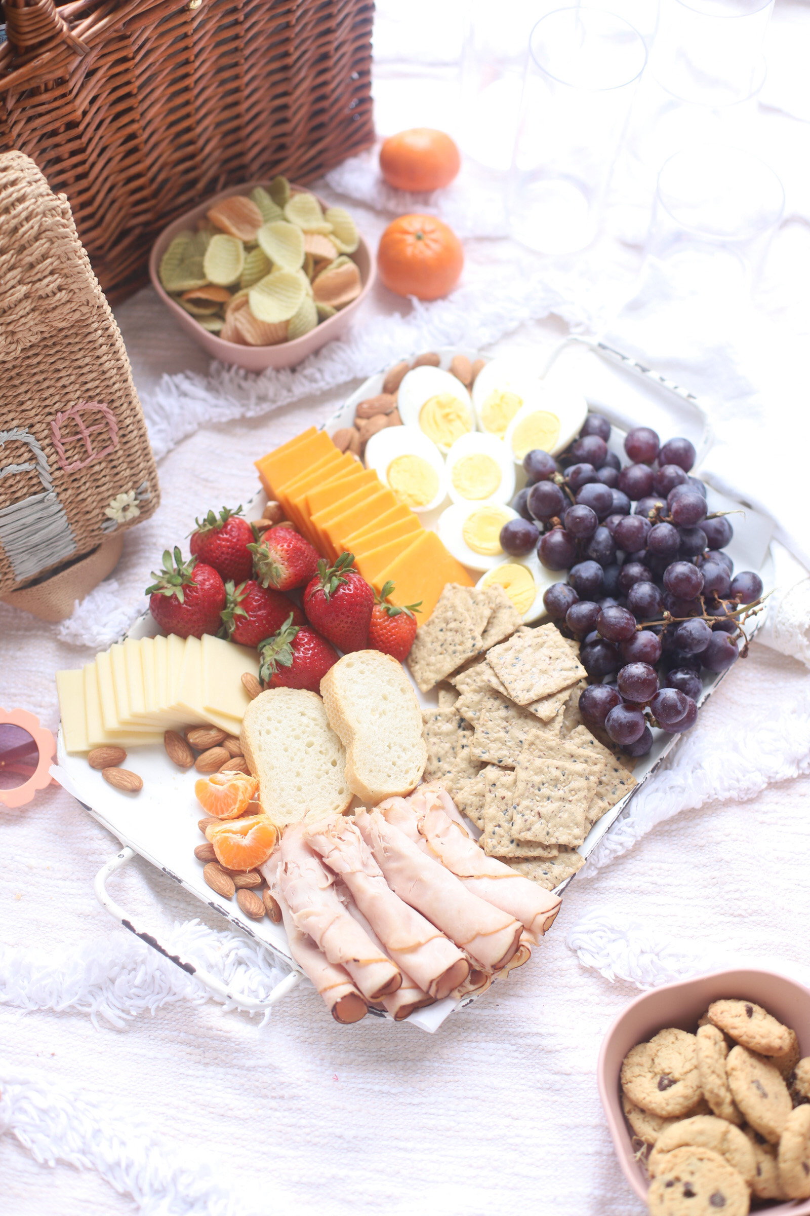 a charcuterie board with fruits, meat. crackers, cheese, and egg