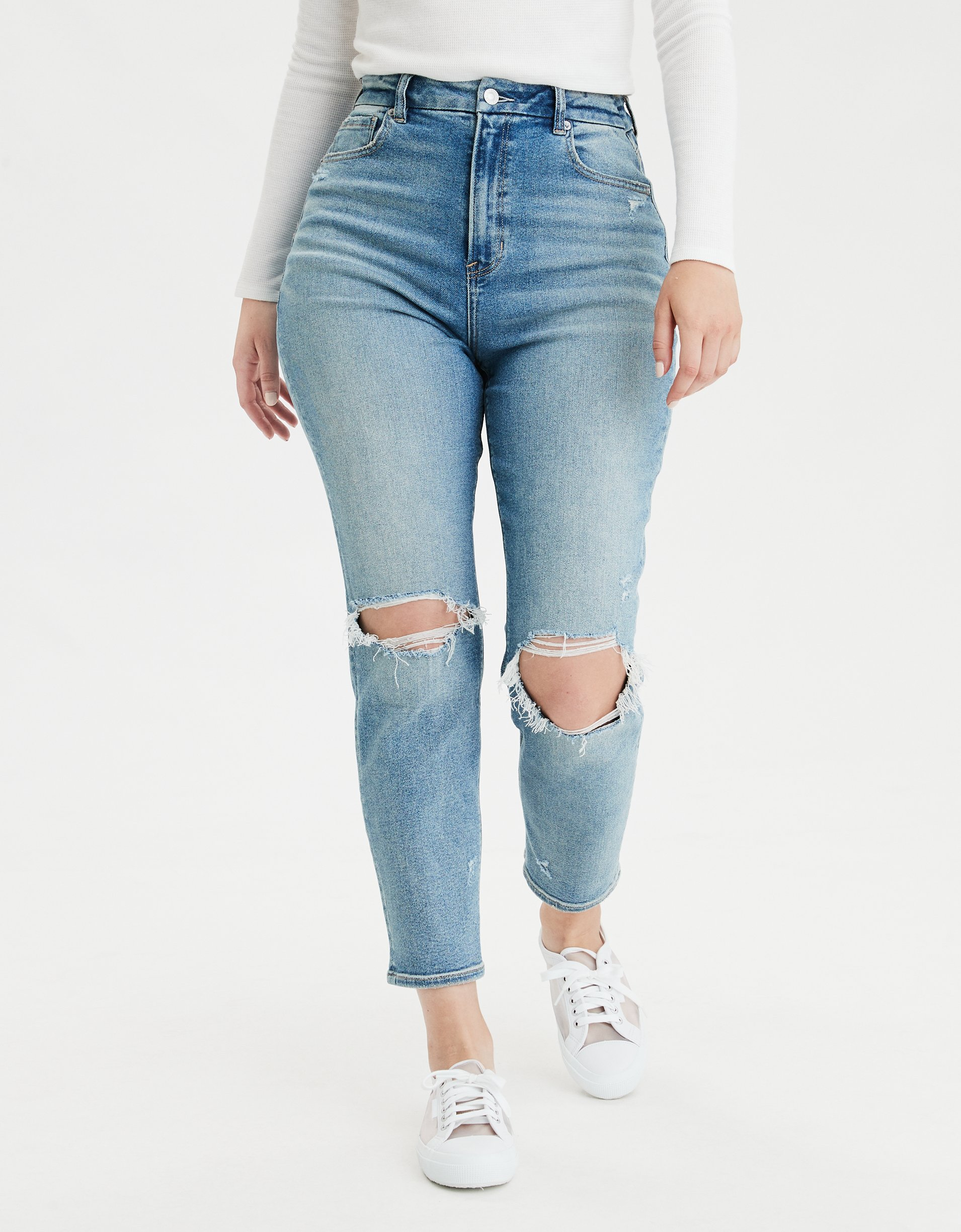 woman wearing AE Stretch Ripped Curvy Mom Jean, white top, and white sneakers