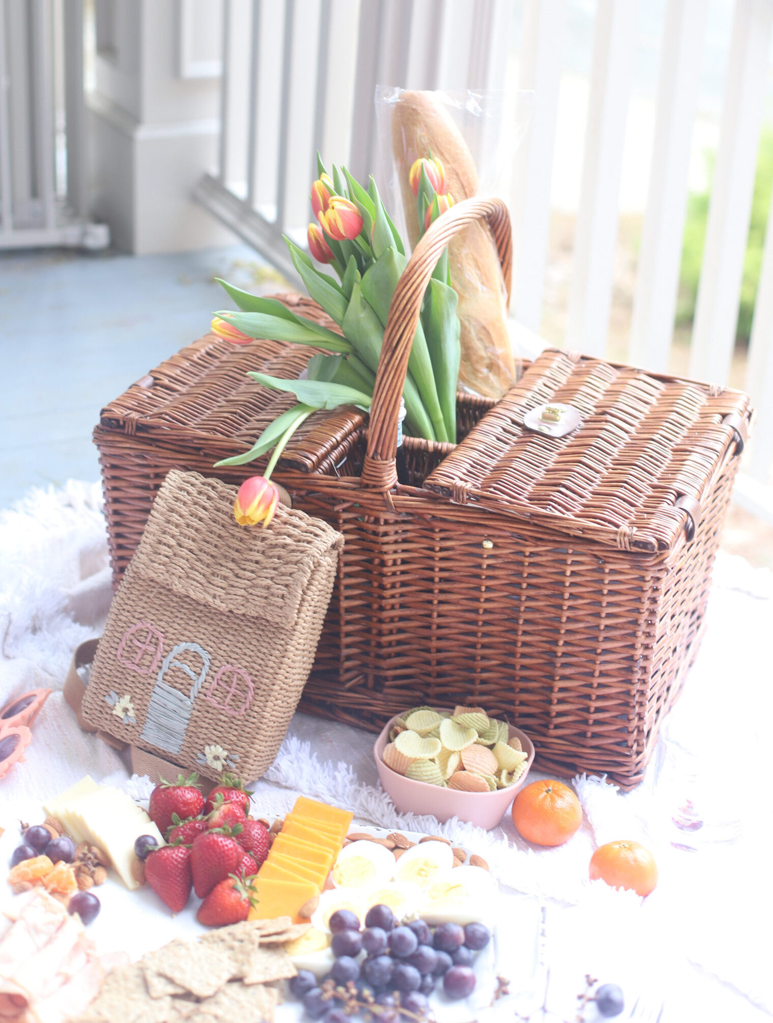 a picnic basket surrounded by fruits, cheese, and crackers