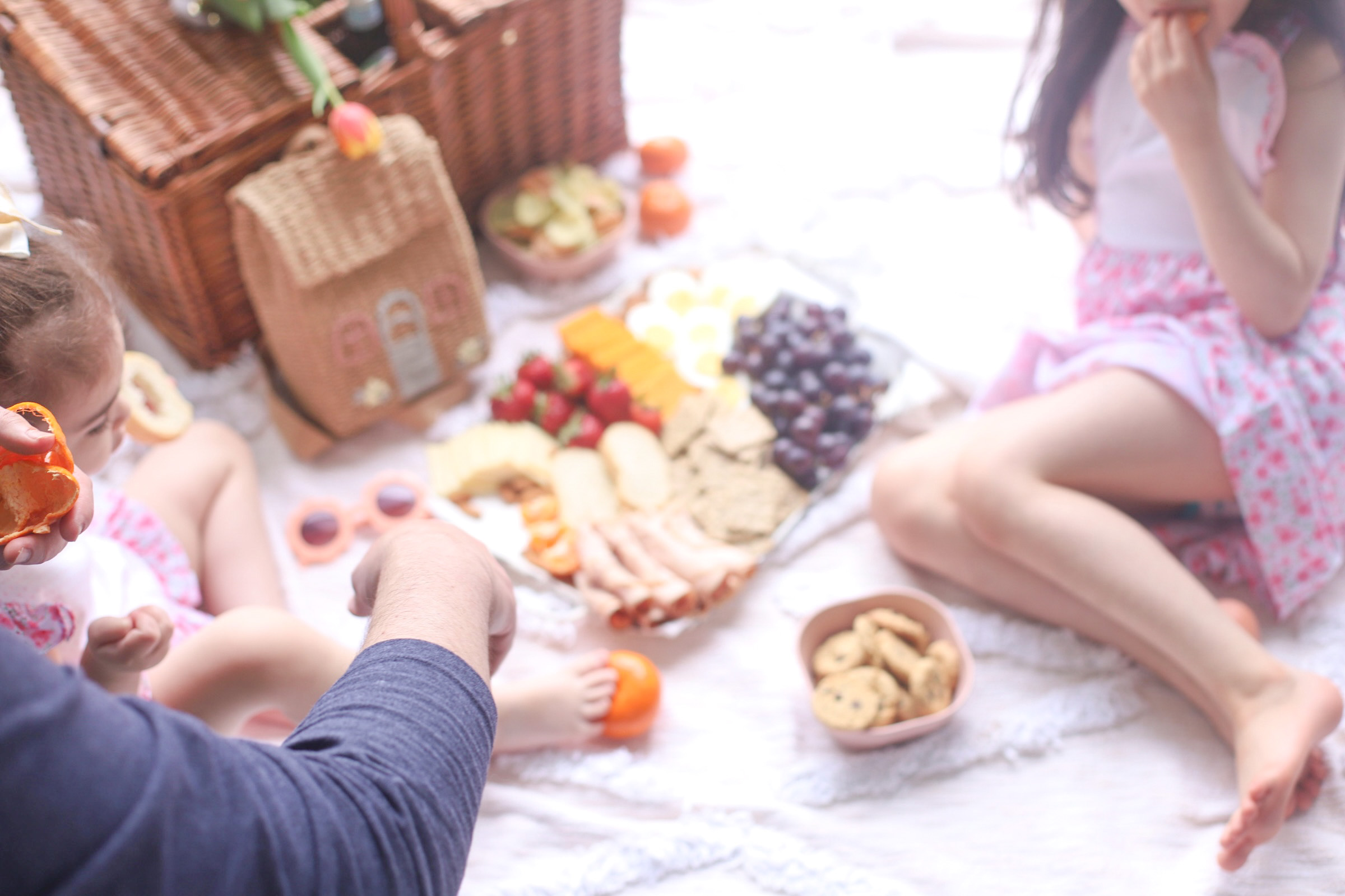 two kids, a picnic basket, and a charcuterie board