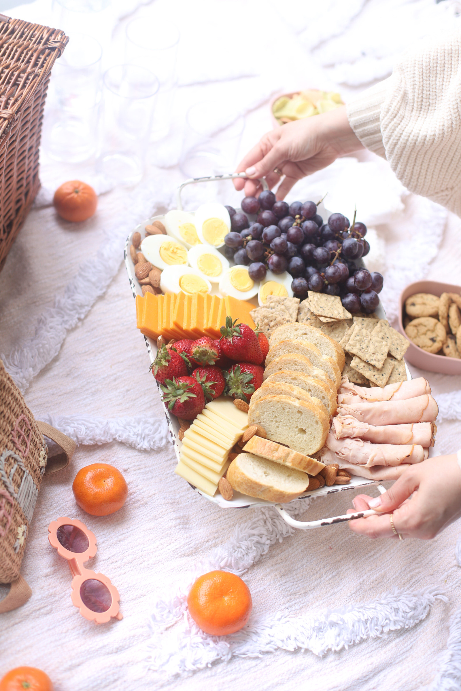 basket full of bread, eggs, fruits, and cheese for Charcuterie Board