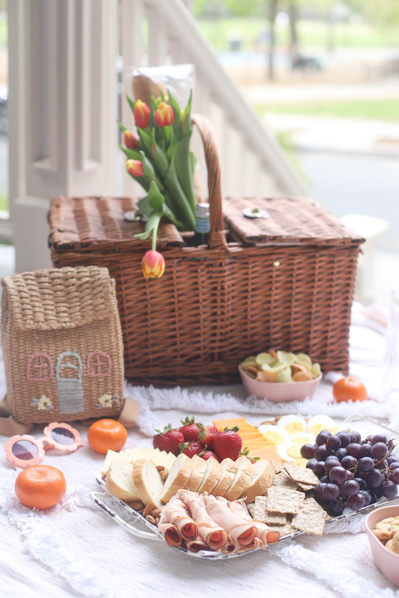 a picnic basket with flowers in it and charcuterie board