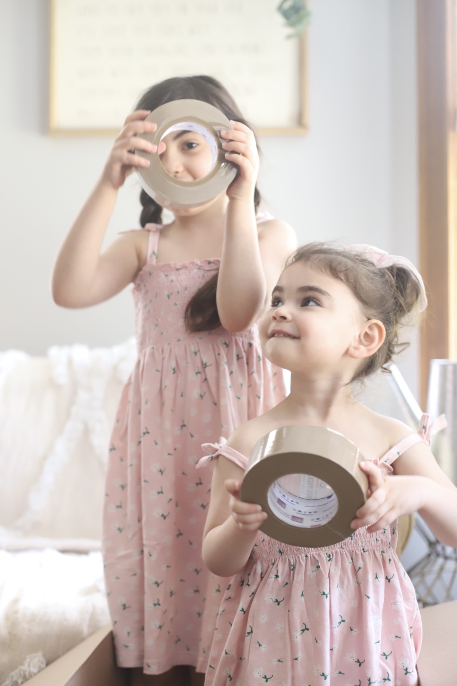 two kids wearing pink dresses and holding packing tapes to show We Bought a House post