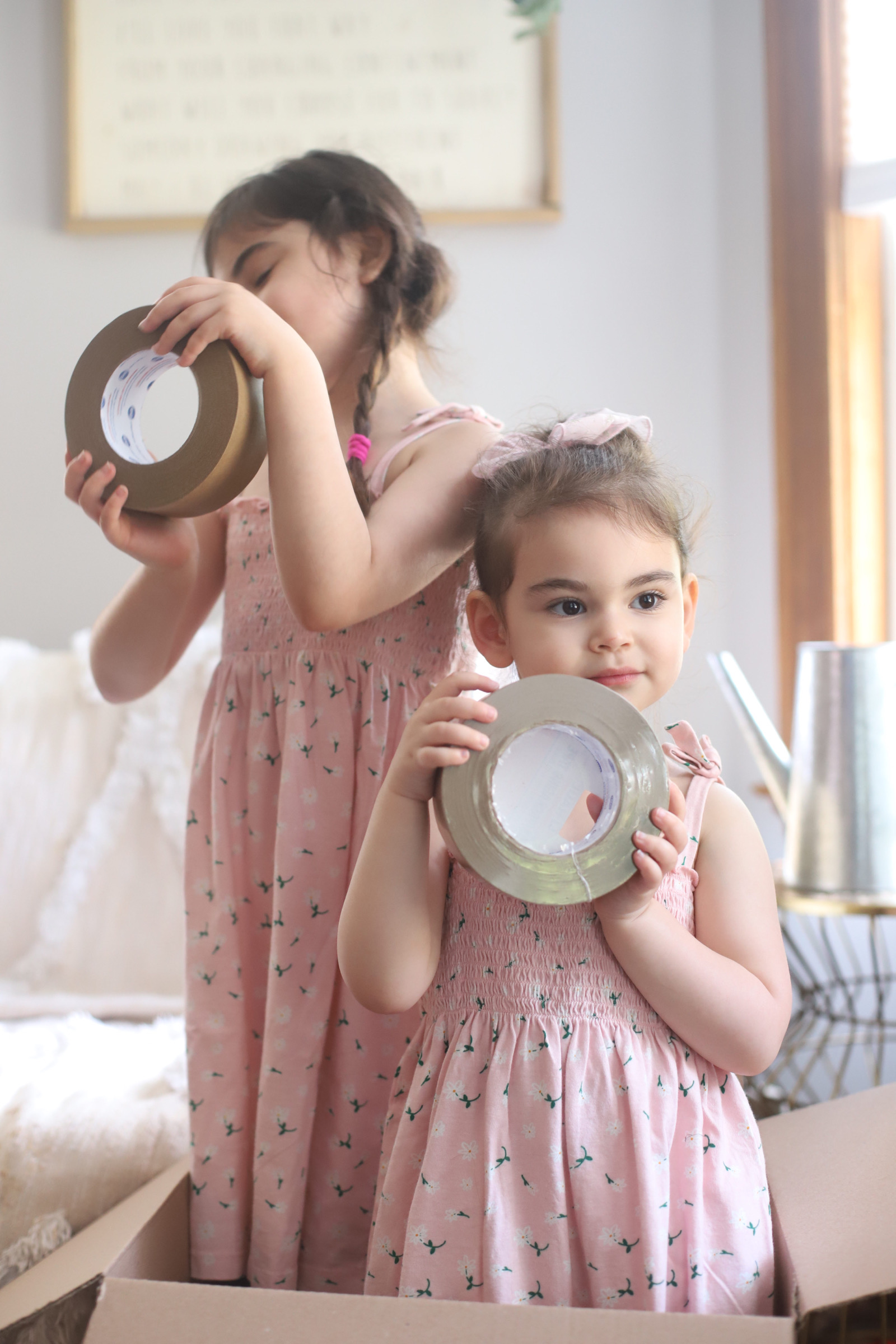two girls wearing pink identical dress and playing with packing tapes