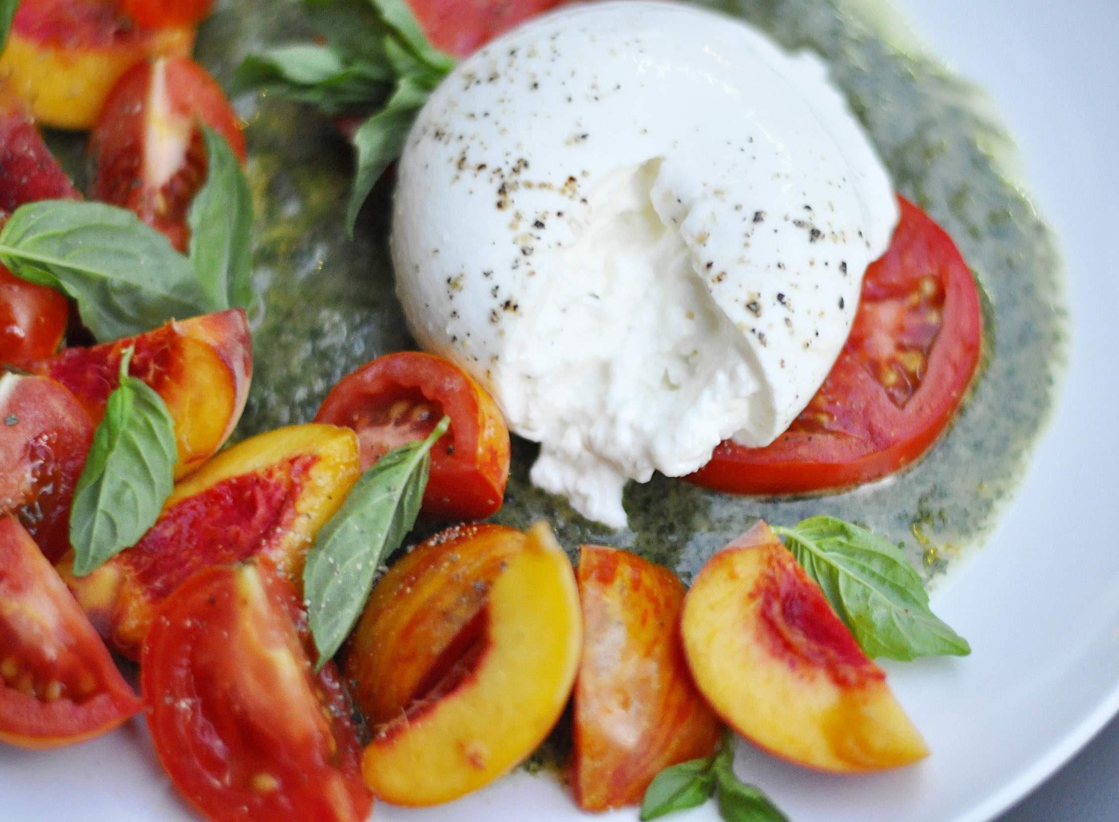 Peach, Tomato, and Burrata Salad on a white plate