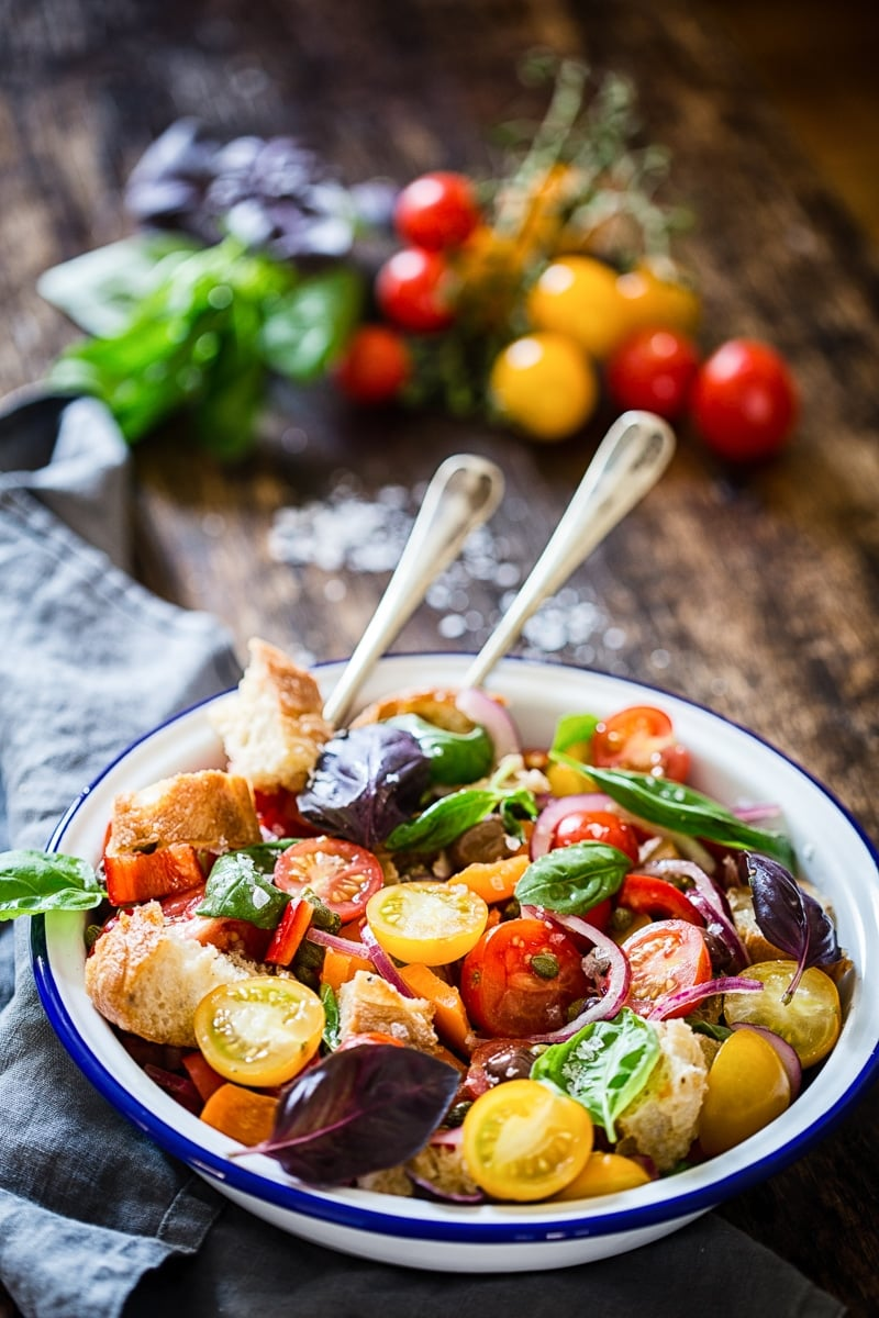 Tuscan Panzanella Salad on a white bowl with two serving spoon for Incredible Summer Salad Recipes
