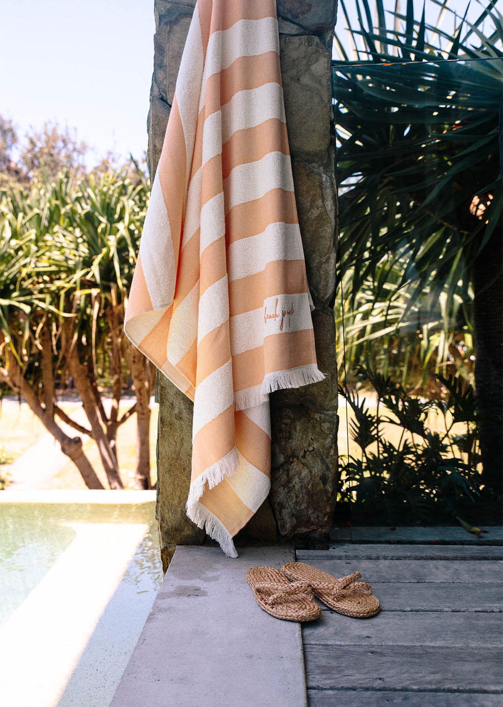 The Beach People Pool Towel hanging near the pool Summer Accessories