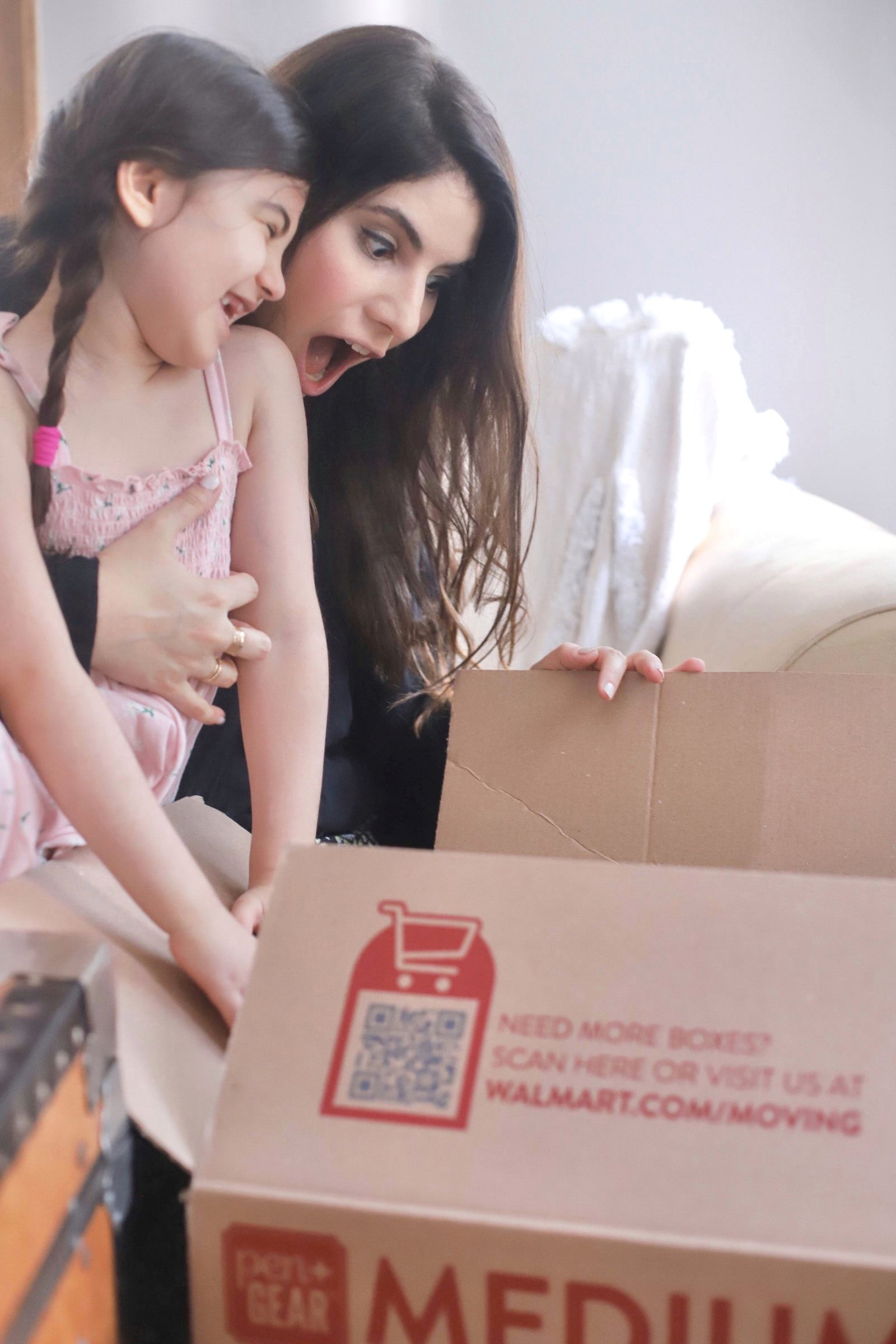 mother and daughter looking at a box in shock