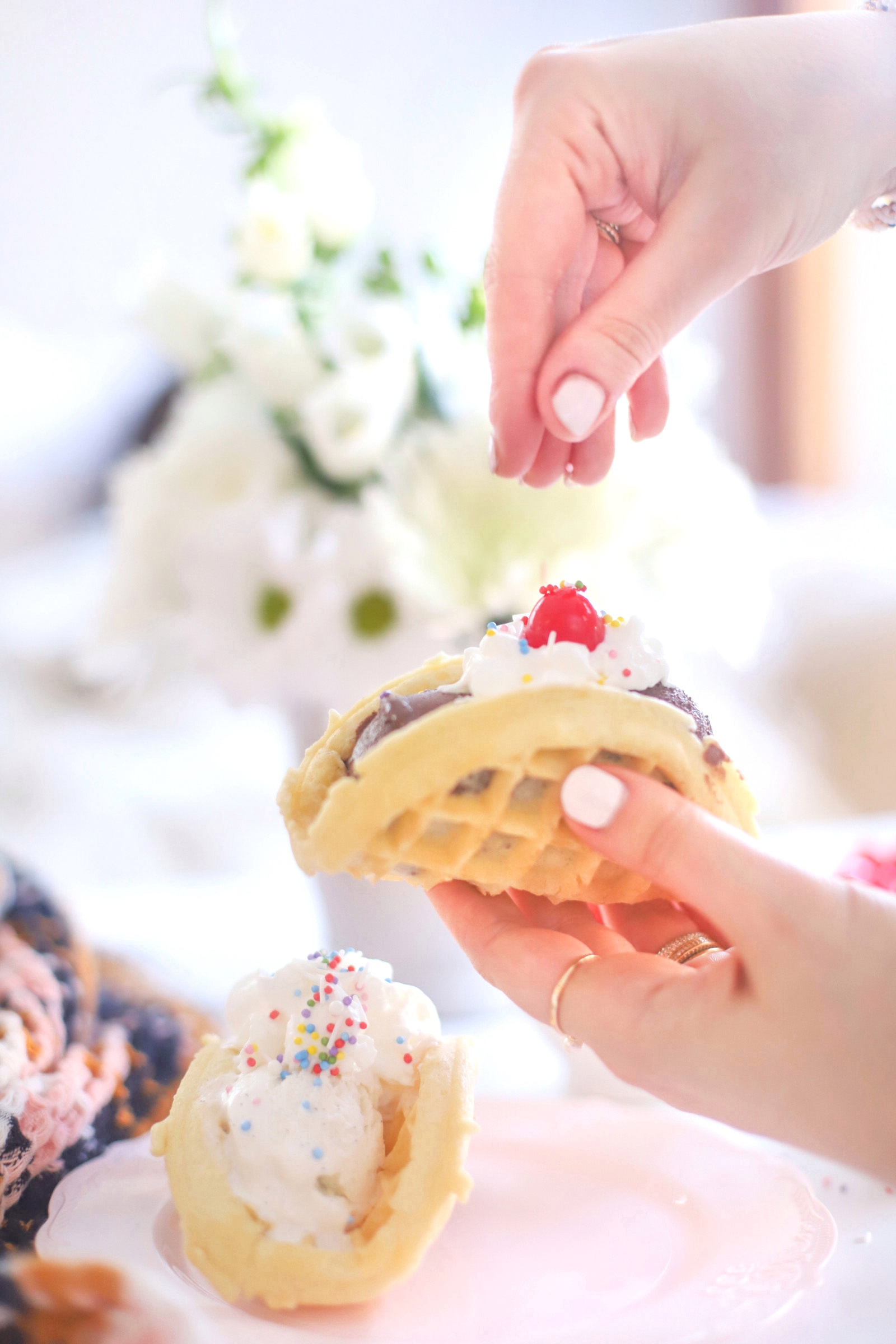 woman sprinkling dessert toppings on a pancake with ice cream