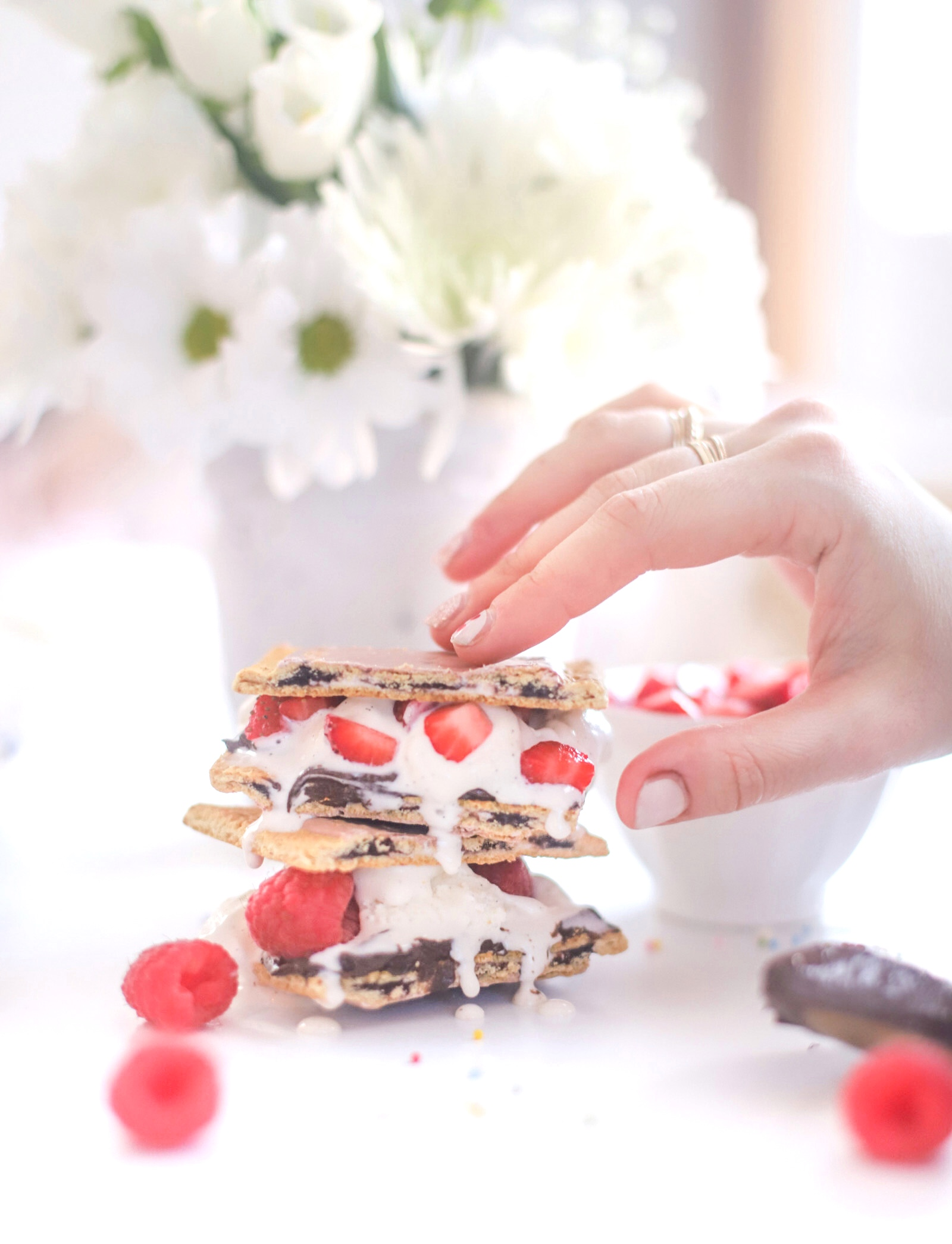 hand holding a dessert with berries and ice cream