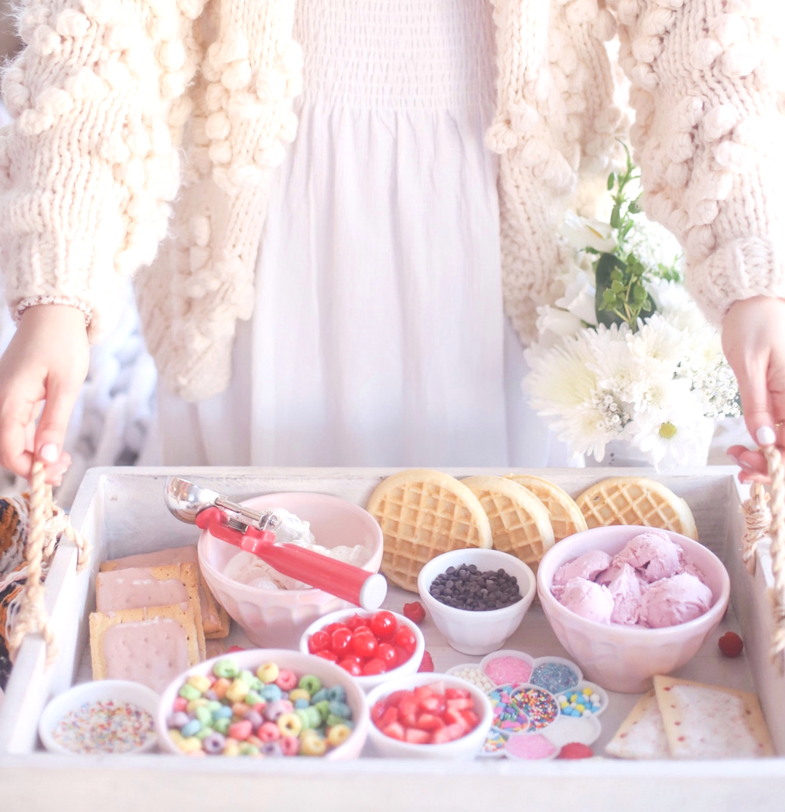 woman holding a tray with Create-Your-Own Ice Cream and toppings