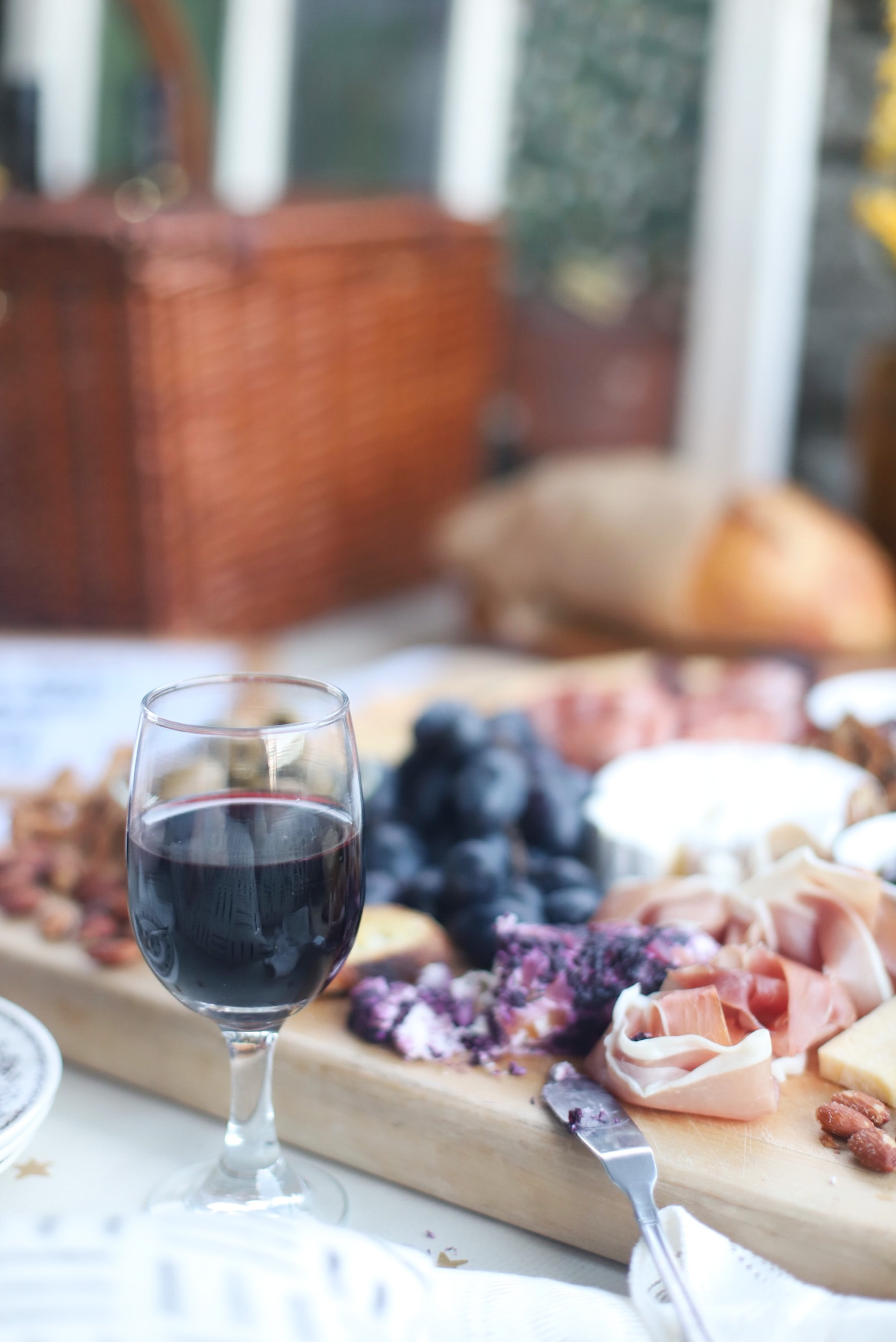 a glass with wine and a Charcuterie board